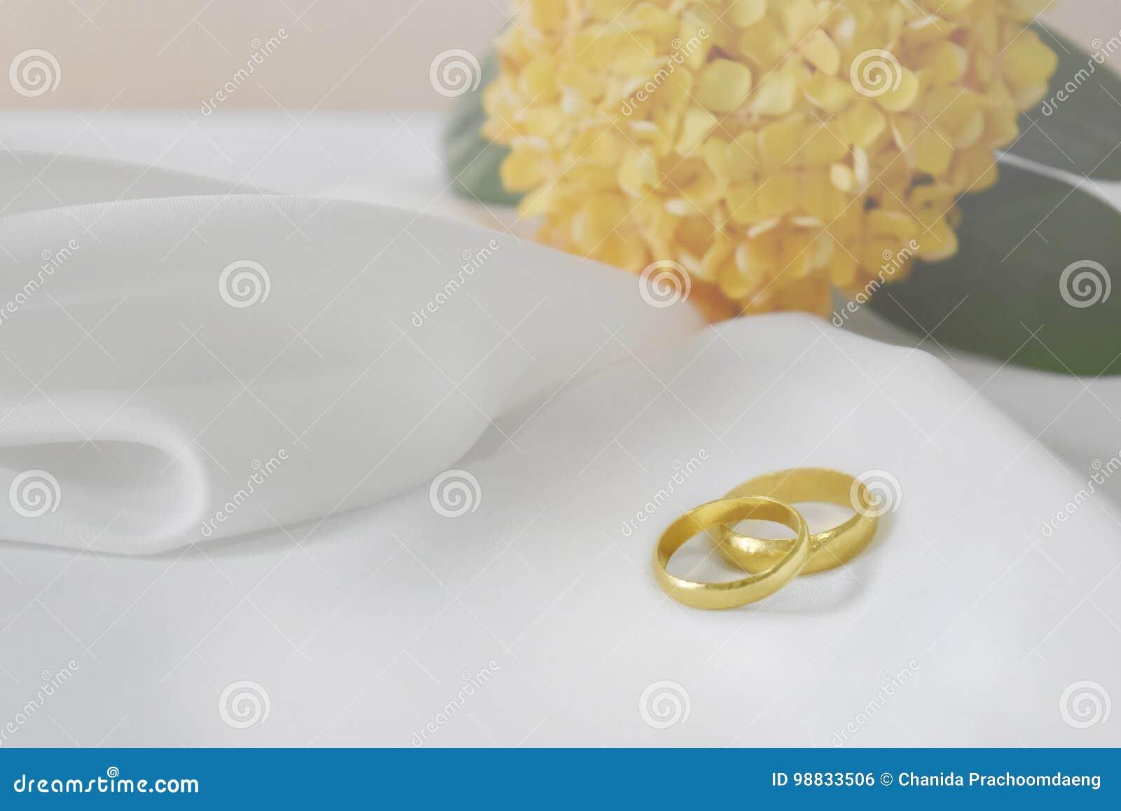 Złocista obrączka ślubna specjalnego dzień W tle jest i opróżnia przestrzeń dla teksta plama kwiat