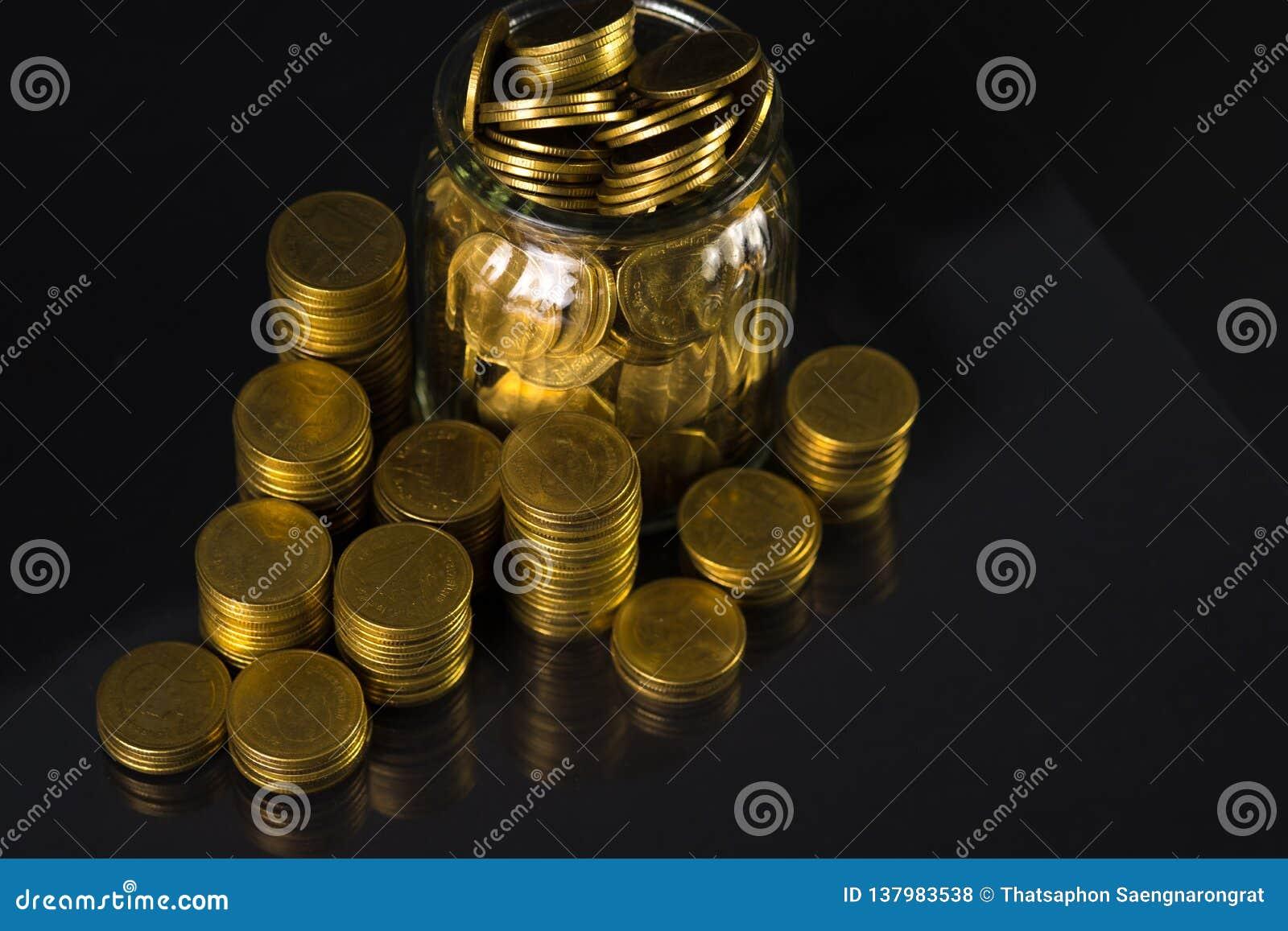 Złocistej monety pieniądze w szklanym słoju na ciemnym tle, dato che finansują pojęcie
