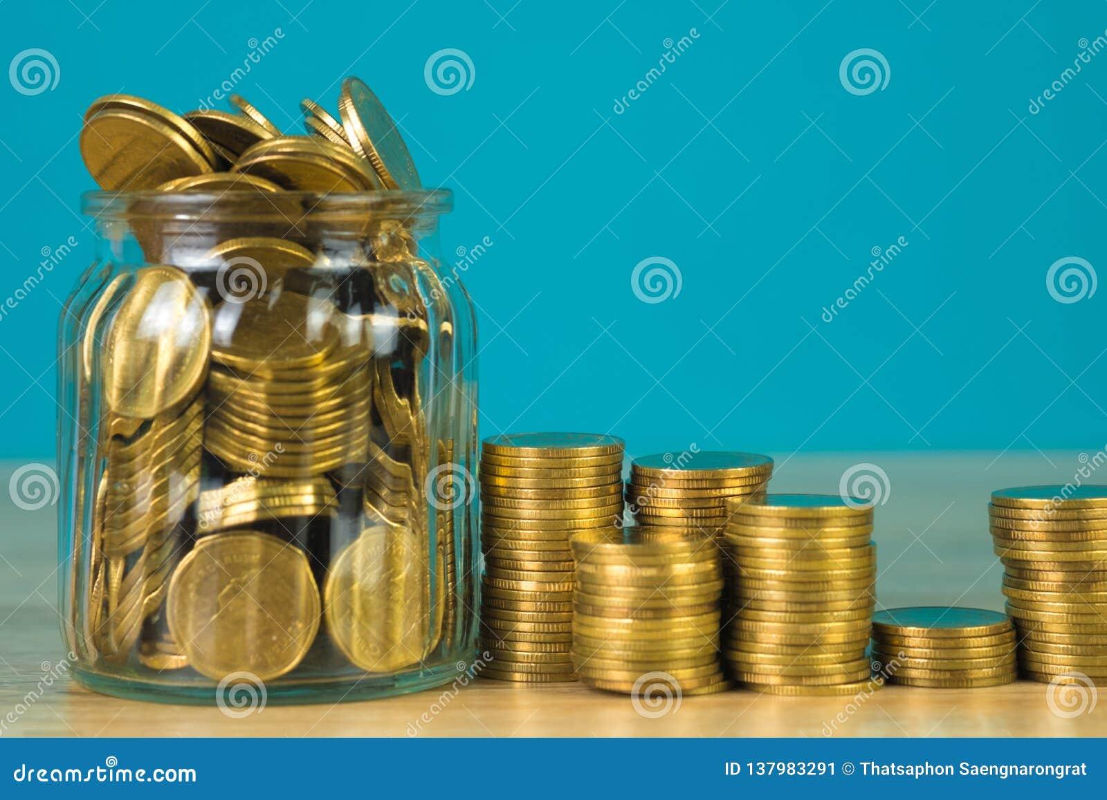 Złocistej monety pieniądze w szklanym słoju na stole z zielonym tłem, dato che