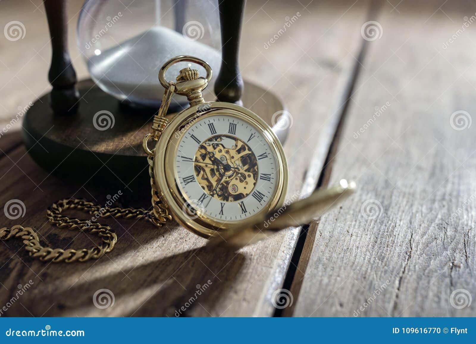 Złocisty kieszeniowy zegarek i hourglass