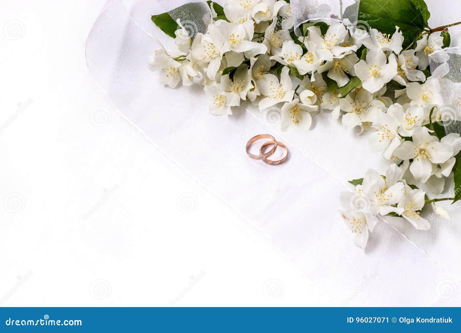 Złocisty pierścionek zaręczynowy z jaśminów faborkami na białym tle i kwiatami