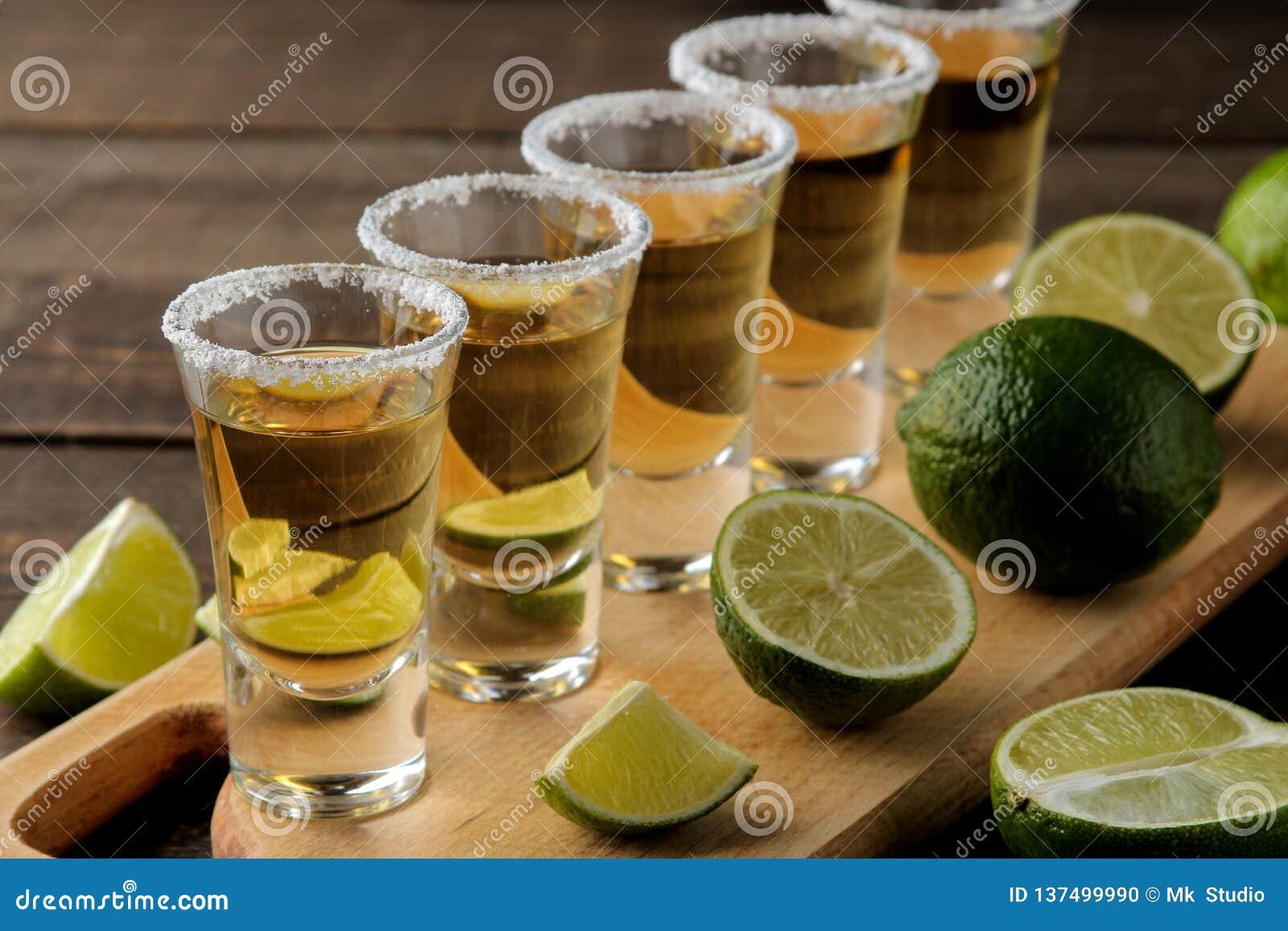 Złocisty tequila w szklanym strzału szkle z solą i wapnem na brązu drewnianym tle bar napoje alkoholowe