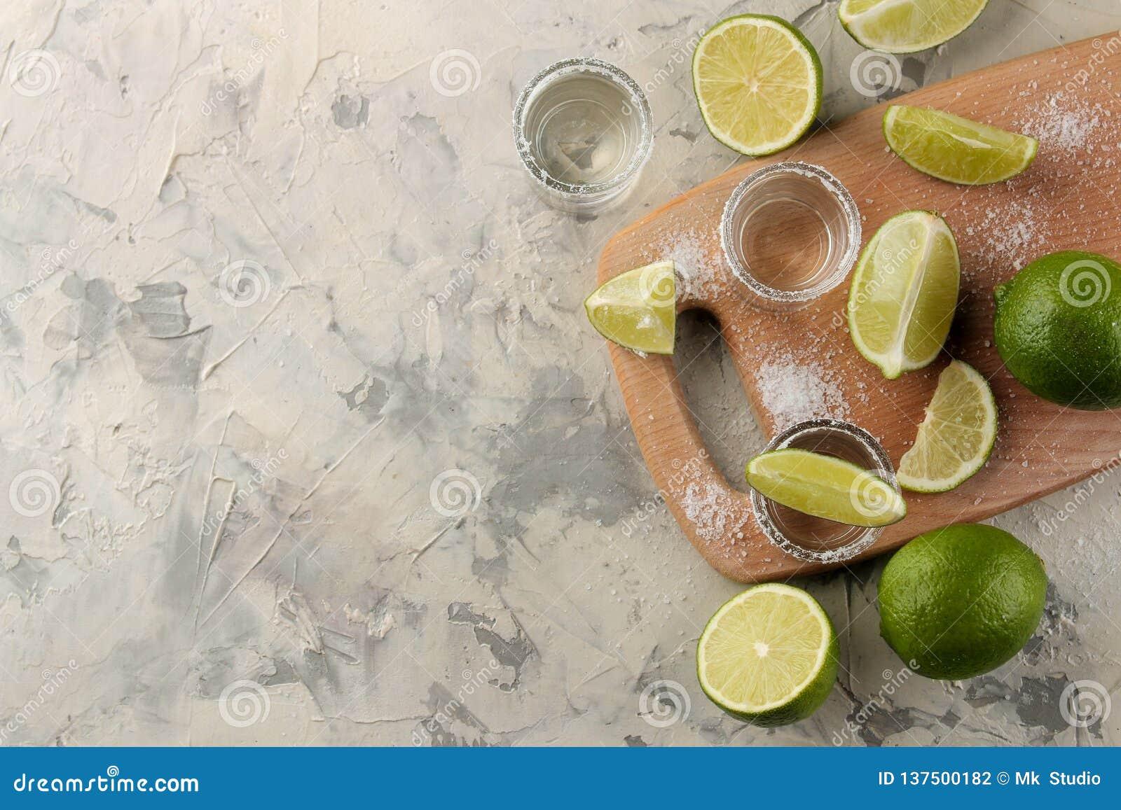 Złocisty tequila w szklanym strzału szkle z solą i wapnem na lekkim betonowym tle bar napoje alkoholowe na widok W