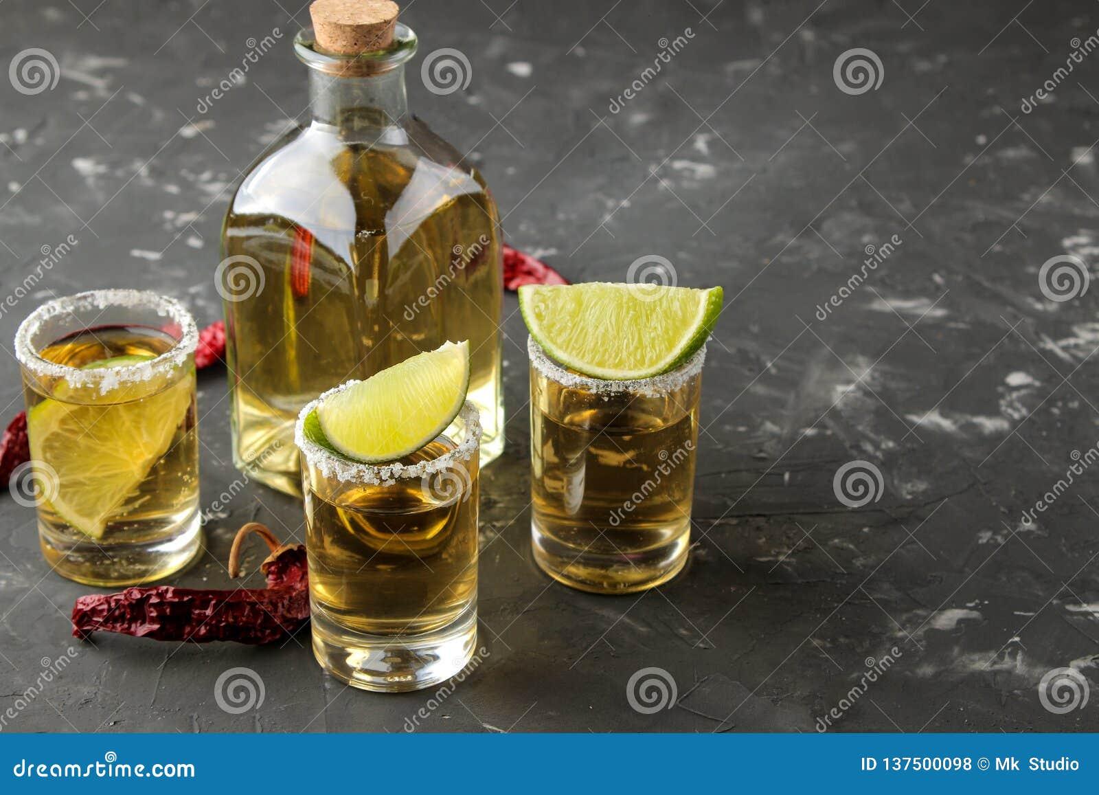 Złocisty tequila w szklanym strzału szkle z solą, wapnem i gorącym pieprzem na czarnym betonowym tle, bar napoje alkoholowe