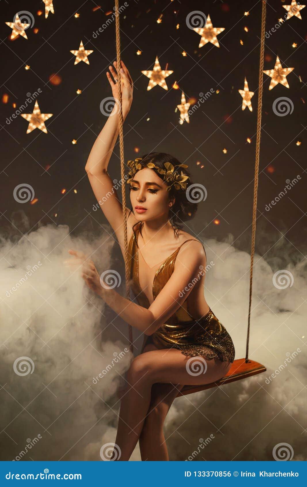 Złota bogini noc, zadziwiająca młoda dziewczyna z ciemnymi wołami i wianek w krótkiej koktajl sukni z siatką,