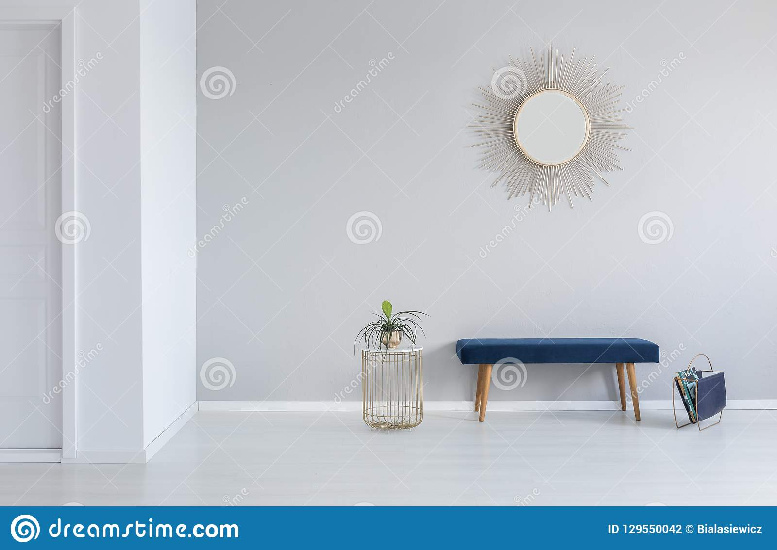 Złota lustro na ścianie nad błękitna ławka w minimalnym pustym wejściowej sali wnętrzu z rośliną