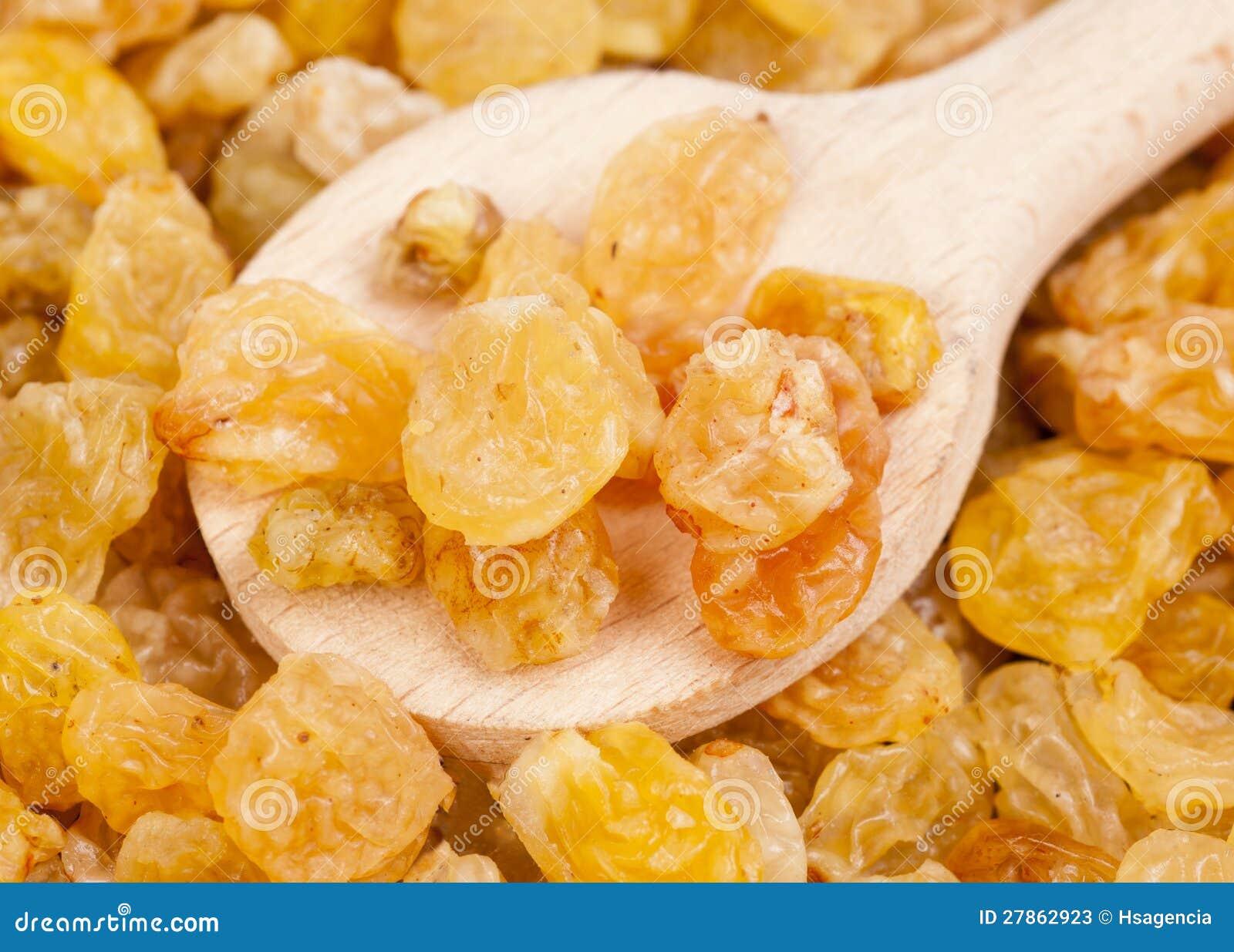 Złote rodzynki close- złotą i drewnianą łyżkę