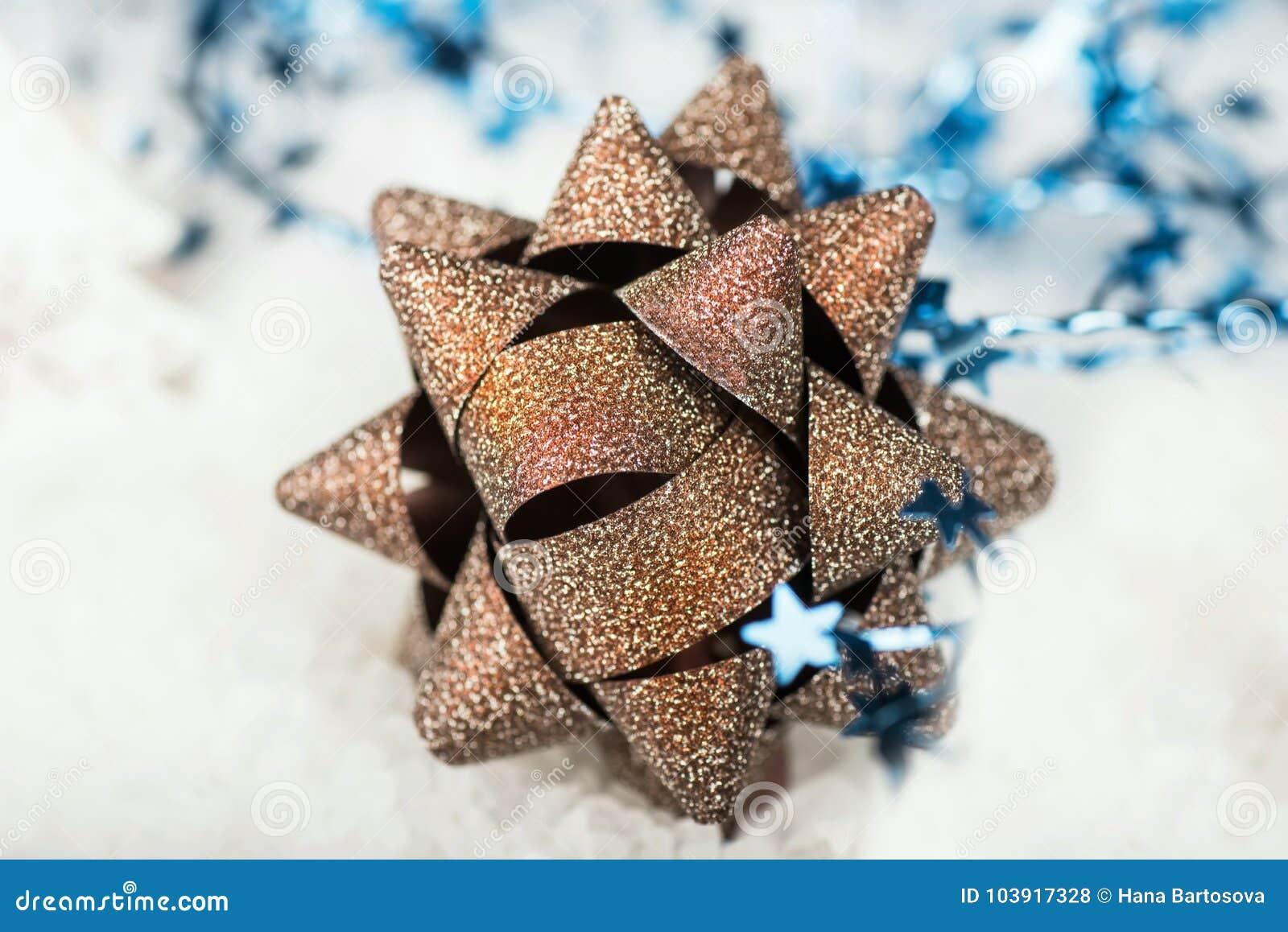 Złoty Bożenarodzeniowy dekoracyjny łęk z błękitnym faborkiem na śniegu
