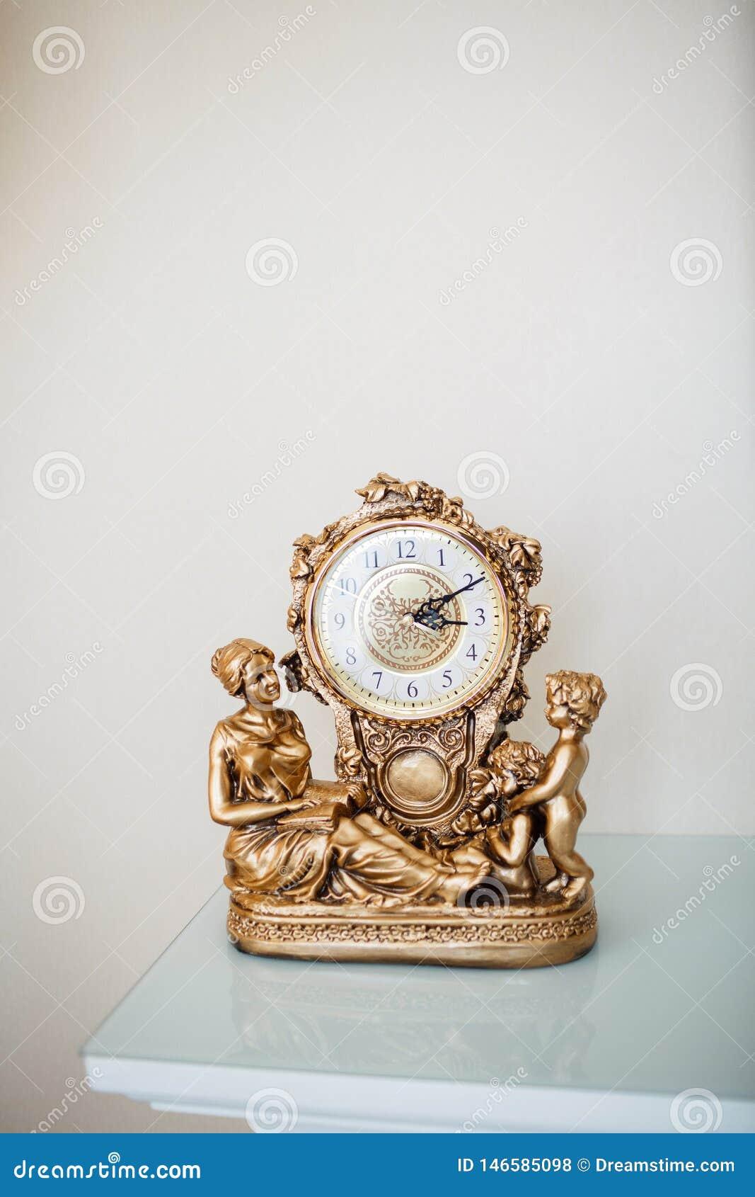 Złoty stołowy zegar dekoruje z postaciami kobieta dwa chłopiec