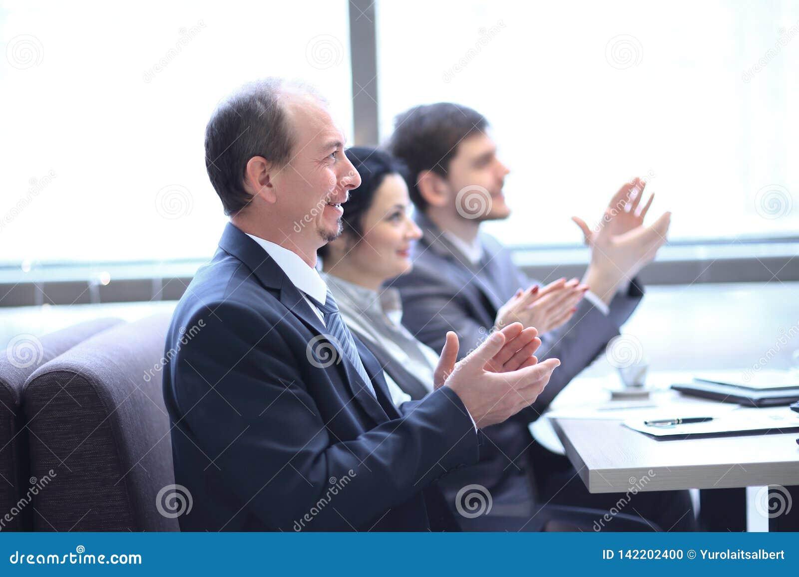 Z bliska biznes drużyna oklaskuje mówcy, siedzi w miejsce pracy