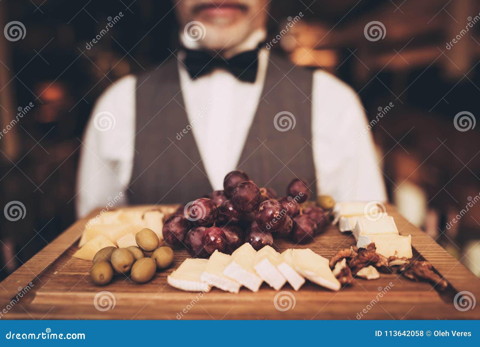 Z bliska Sommelier trzyma przekąski dla czerwonego wina na drewnianym talerzu Winogrona Ser oliwki walsh