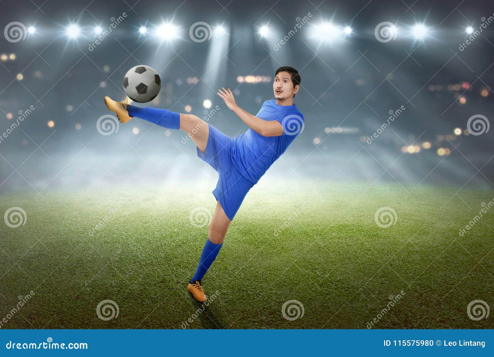 Z podnieceniem azjatykci futbolista pokazuje jego umiejętność