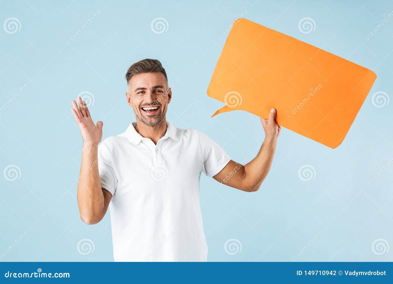 Z podnieceniem emocjonalny dorosły mężczyzny pozować odizolowywam nad błękit ściany tła mienia mowy bąblem