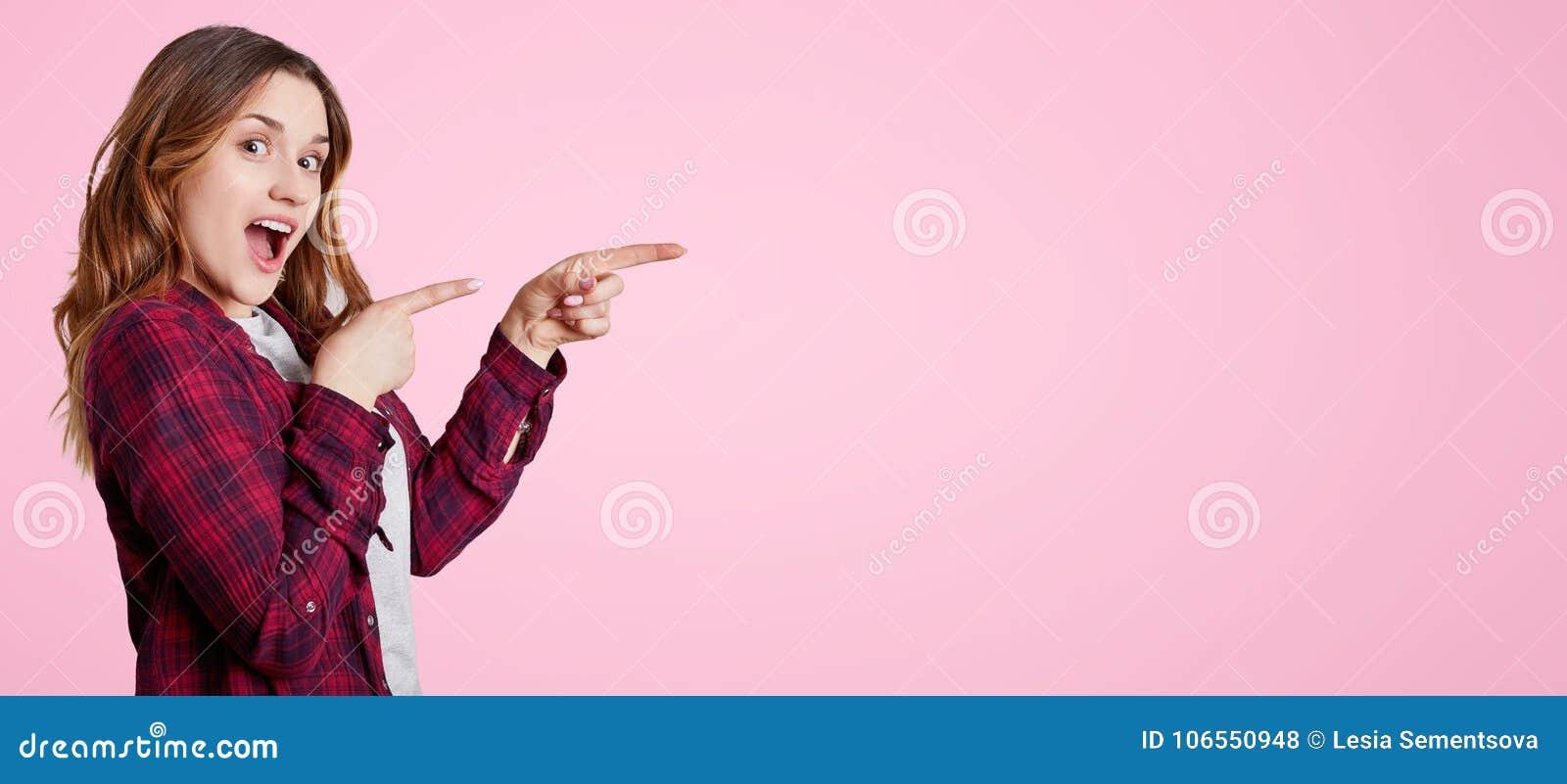 Z podnieceniem piękna kobieta stoi z ukosa, jest ubranym chemise, punkty z pierwszych planów palcami przy puste miejsce kopii prz