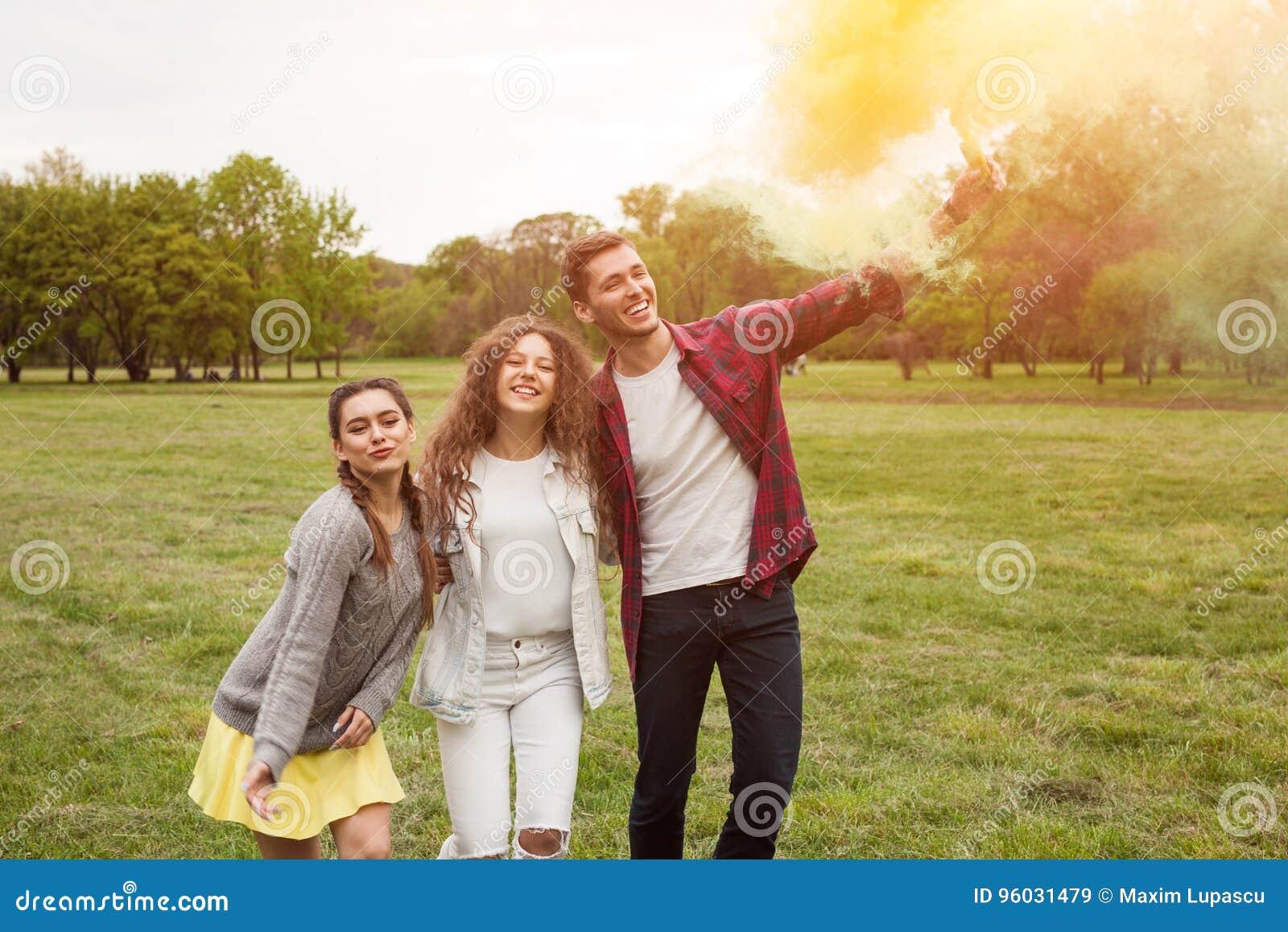 Z podnieceniem przyjaciele z barwionym dymem w parku