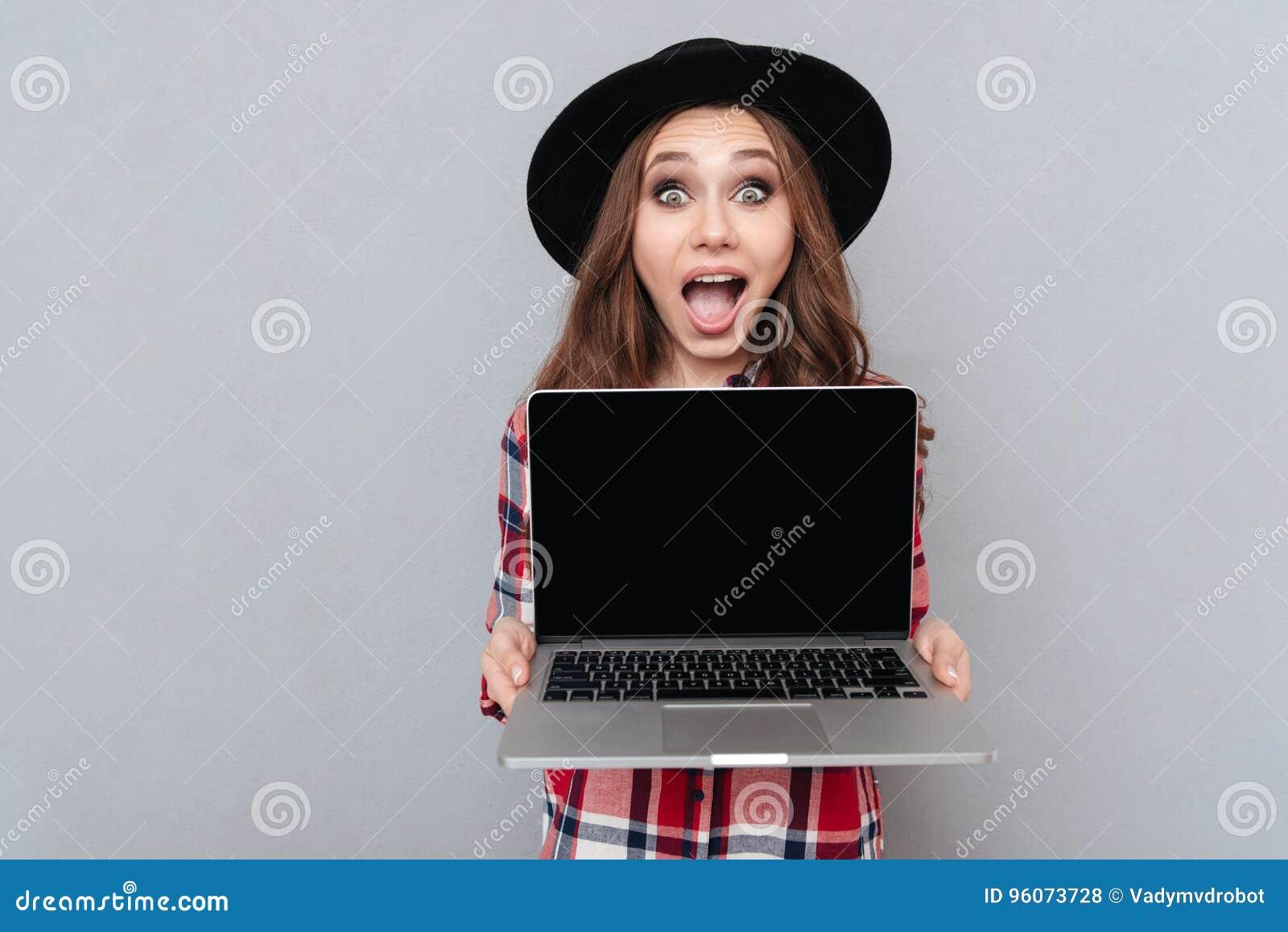 Z podnieceniem przypadkowa dziewczyna trzyma pustego ekranu laptop w szkockiej kraty koszula