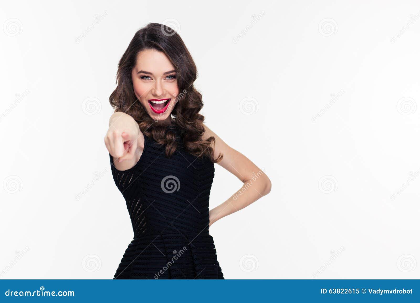 Z podnieceniem szczęśliwa ufna kędzierzawa retro projektująca kobieta wskazuje przy kamerą