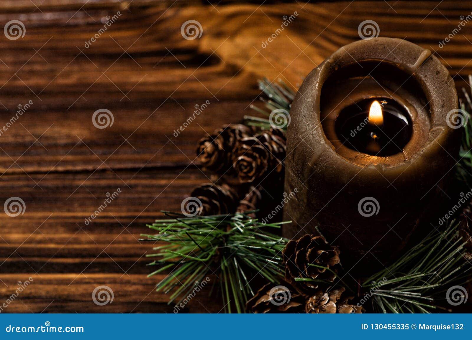 Zaświecająca brąz świeczka dekoruje z świerkową gałąź z małymi rożkami Brown drewniane deski na tle