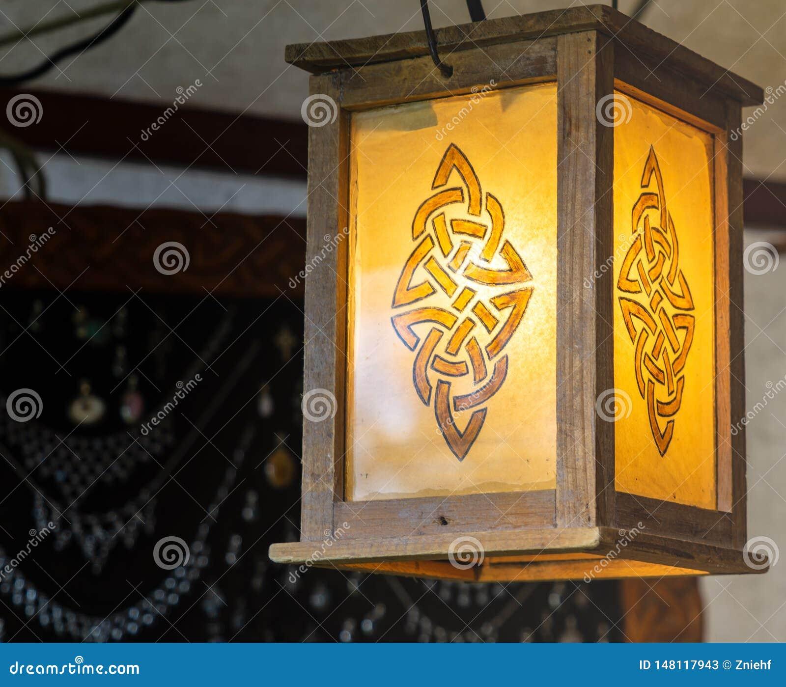 Zaświecający lampion z abstrakcjonistycznym wzorem przypomina rune, drewniana rama z żółtym szkłem