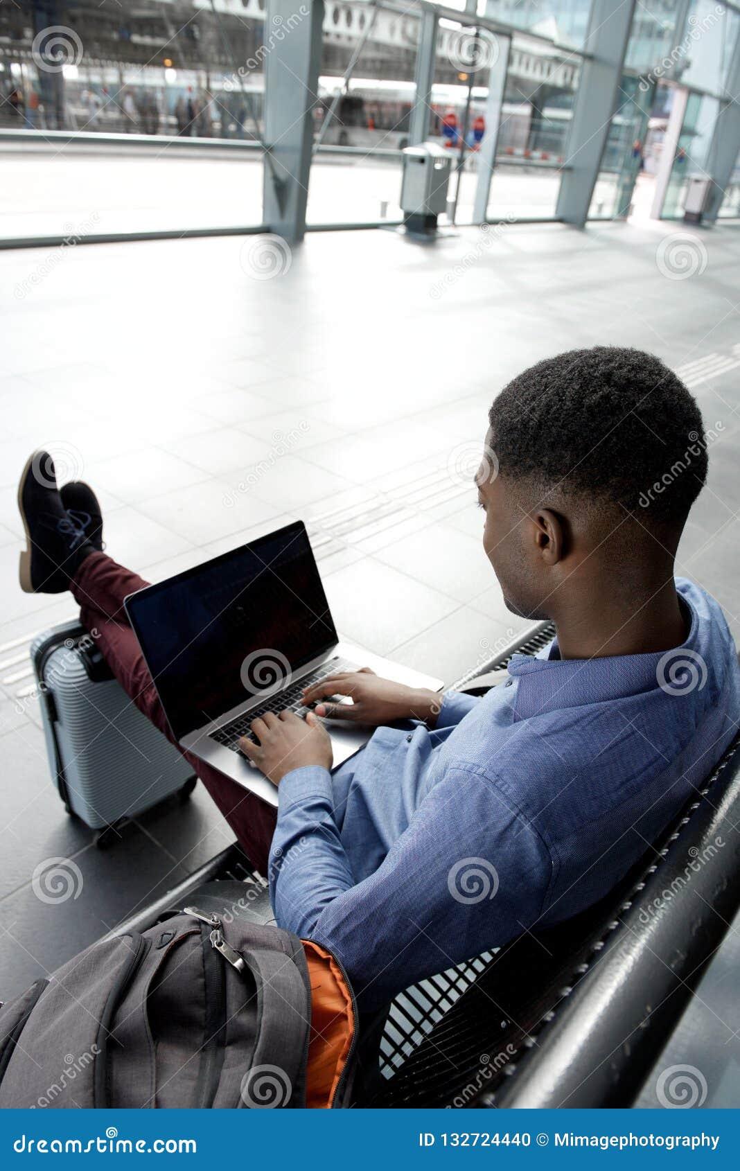Za amerykanin afrykańskiego pochodzenia biznesmena podróżnym czekaniem na ławce z torbami i laptopem