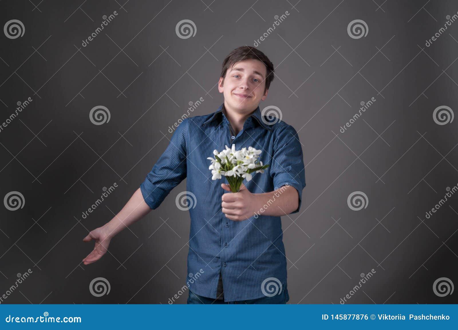 Zaaferowany młody człowiek w błękitnym koszulowym mienie bukiecie z śnieżyczkami, patrzeje kamerę i ono uśmiecha się