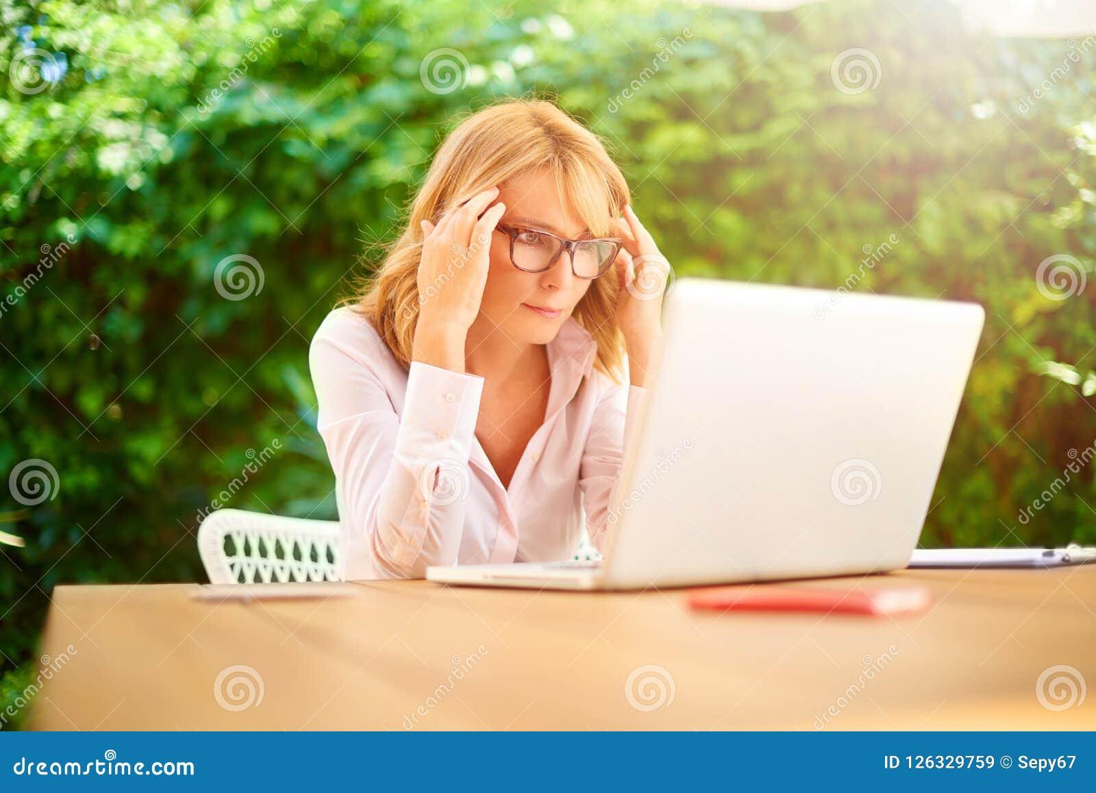 Zaakcentowana kobieta z migreny obsiadaniem przed laptopem