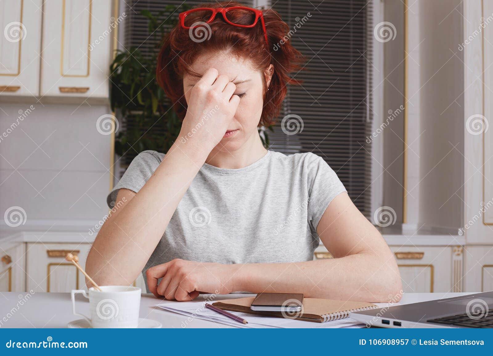 Zaakcentowanego zmęczenia młoda kobieta jest przepracowywającymi się próbami koncentrować, otacza z papierami i nowożytnymi techn