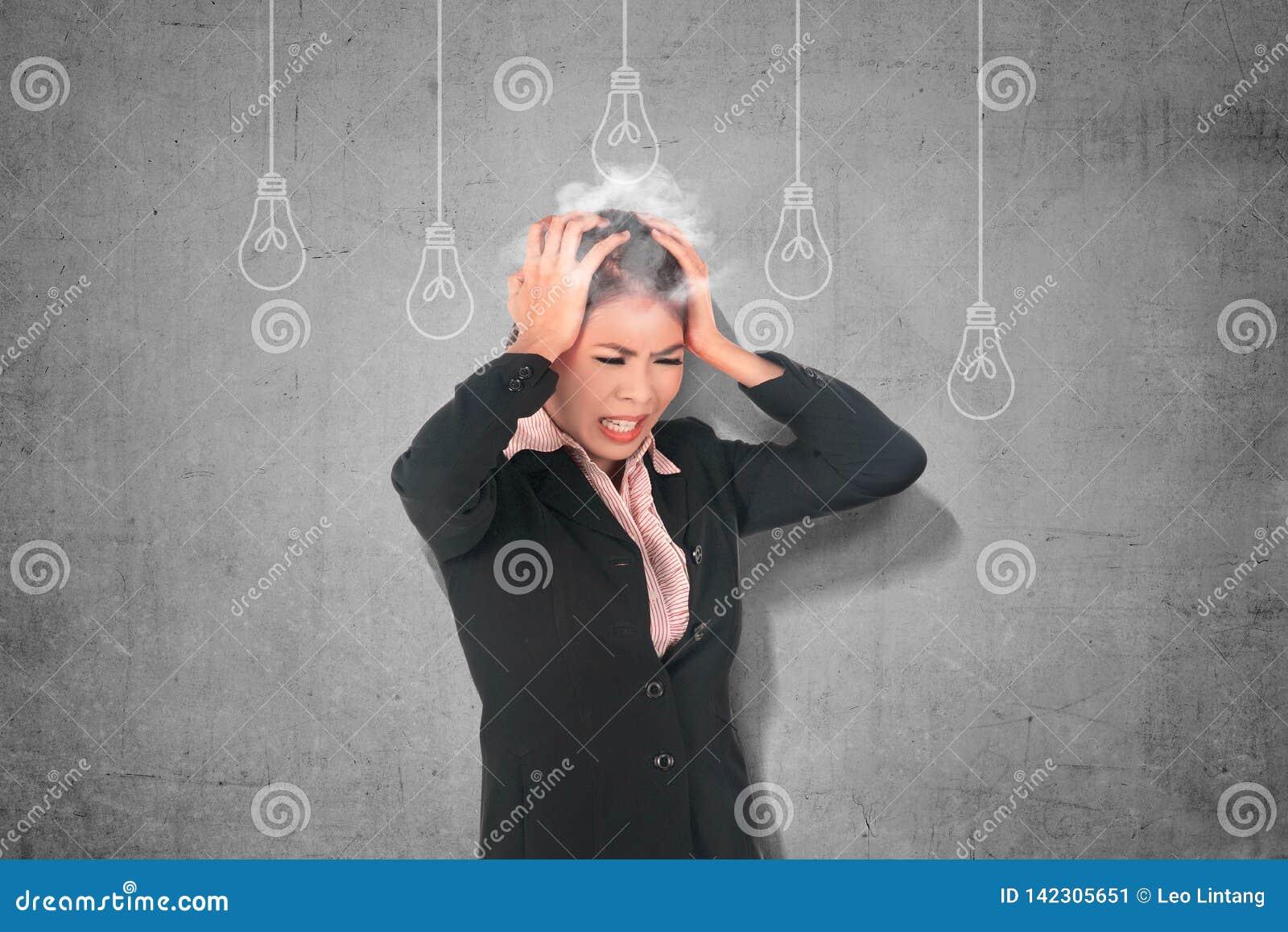 Zaakcentowany azjatykci biznesowej kobiety główkowanie dla nowego kreatywnie pomysłu z żarówki obwieszeniem