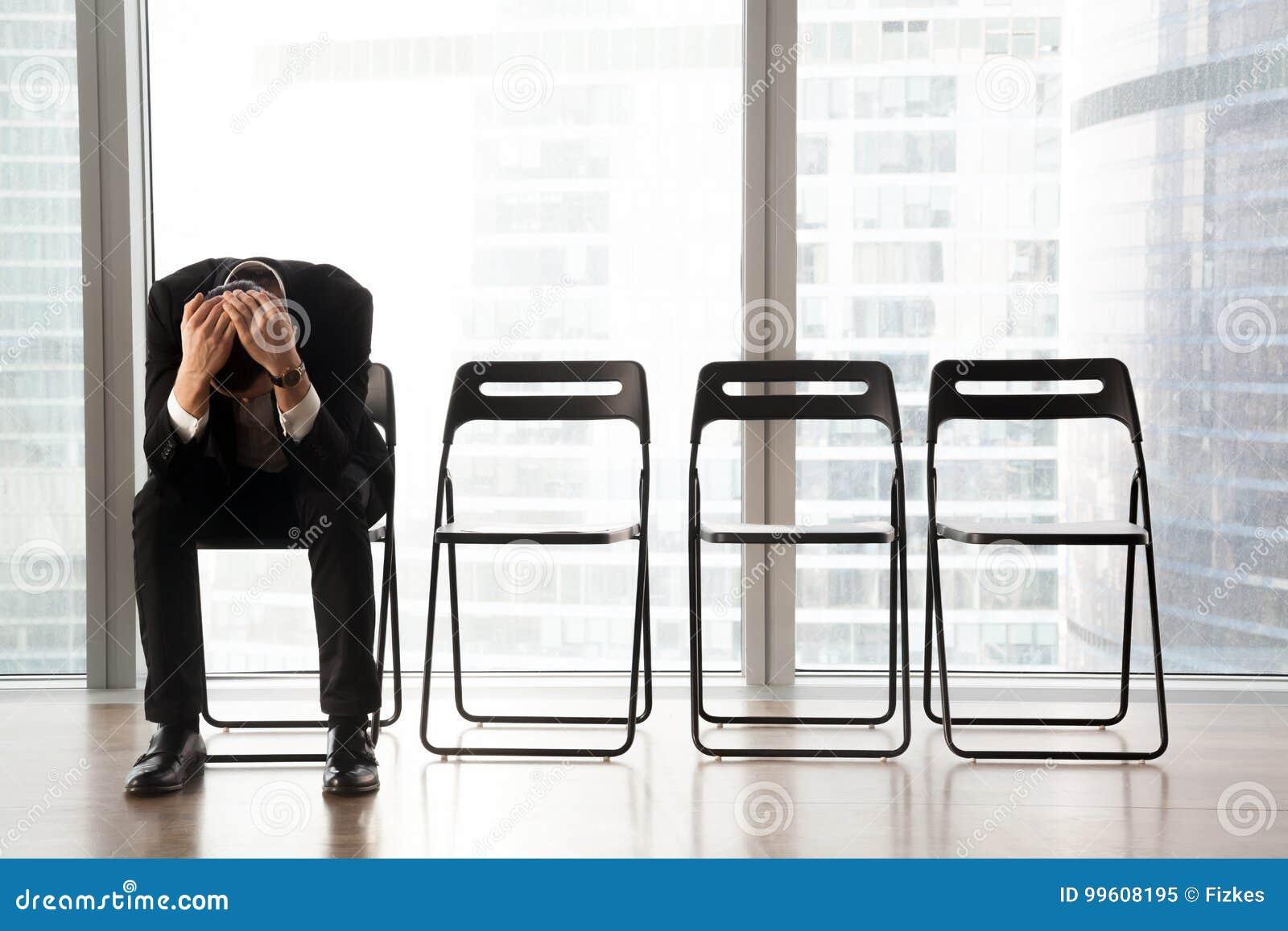 Zaakcentowany wzburzony biznesmena obsiadanie na krześle, otrzymywająca zła wiadomość