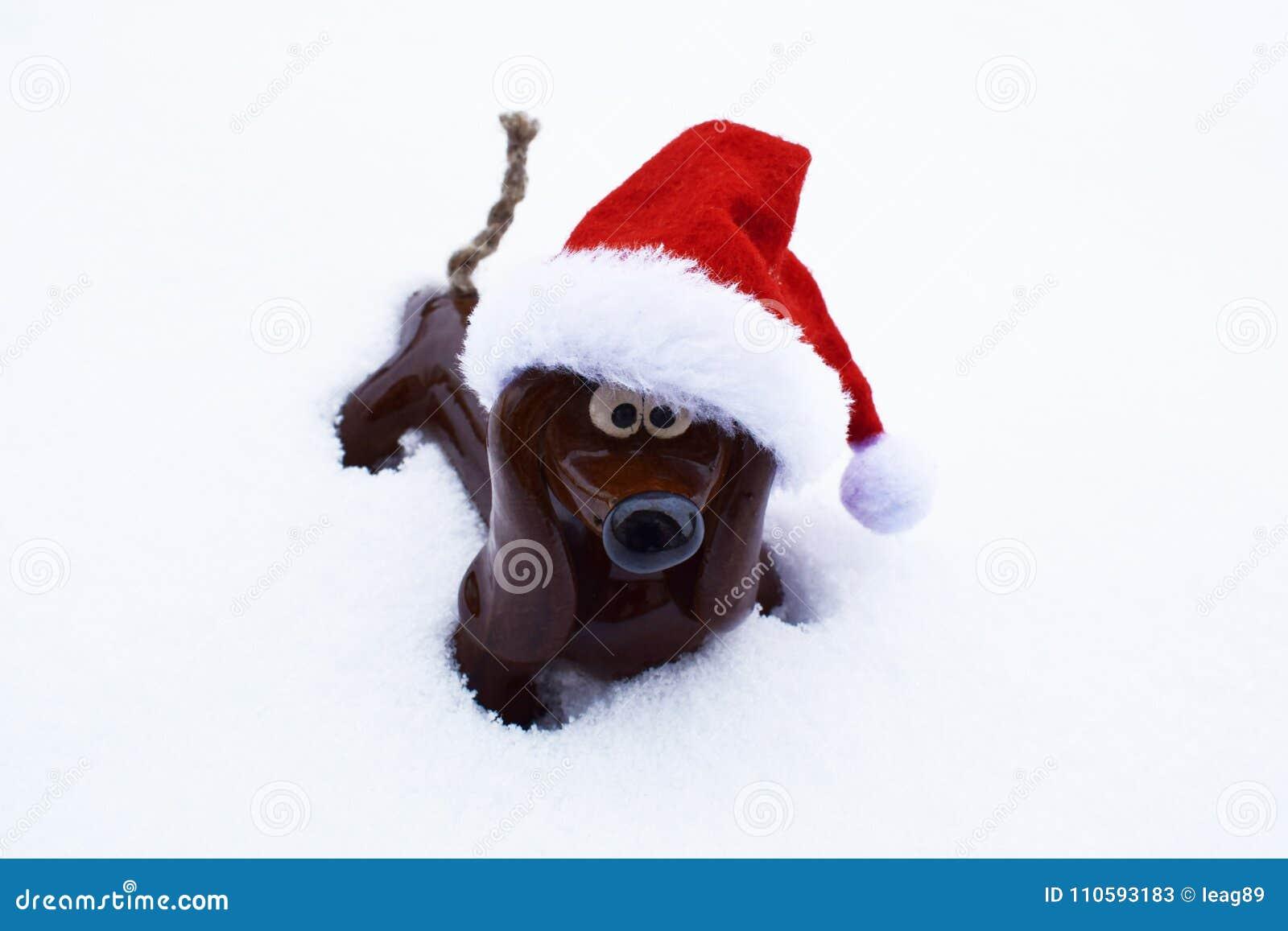 Zabawkarski pies z kapeluszem w śniegu