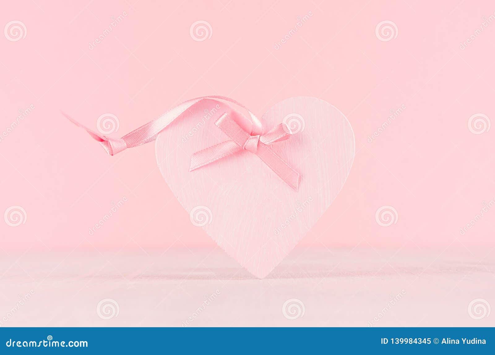 Zacht decor voor Valentine-dagen - zacht lichtrose hart met lint op witte houten raad, close-up
