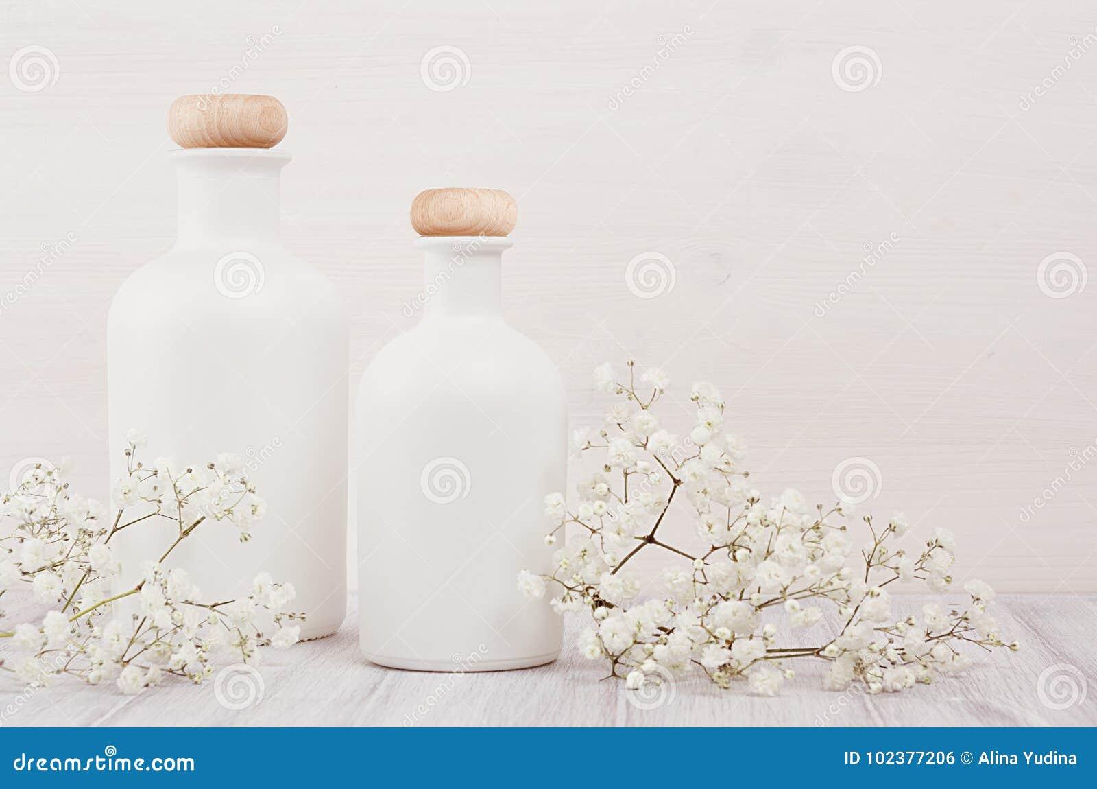 Zacht elegant huisdecor met witte flessen en kleine bloemen op witte houten plank voor reclame, ontwerpers, het brandmerken ident
