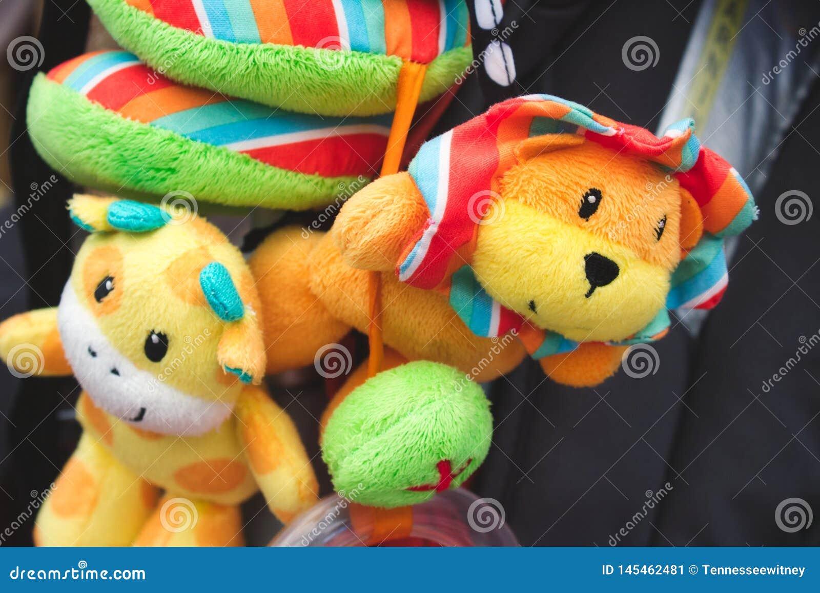 Zacht snoezig speelgoed die van de kinderwagen van een baby hangen