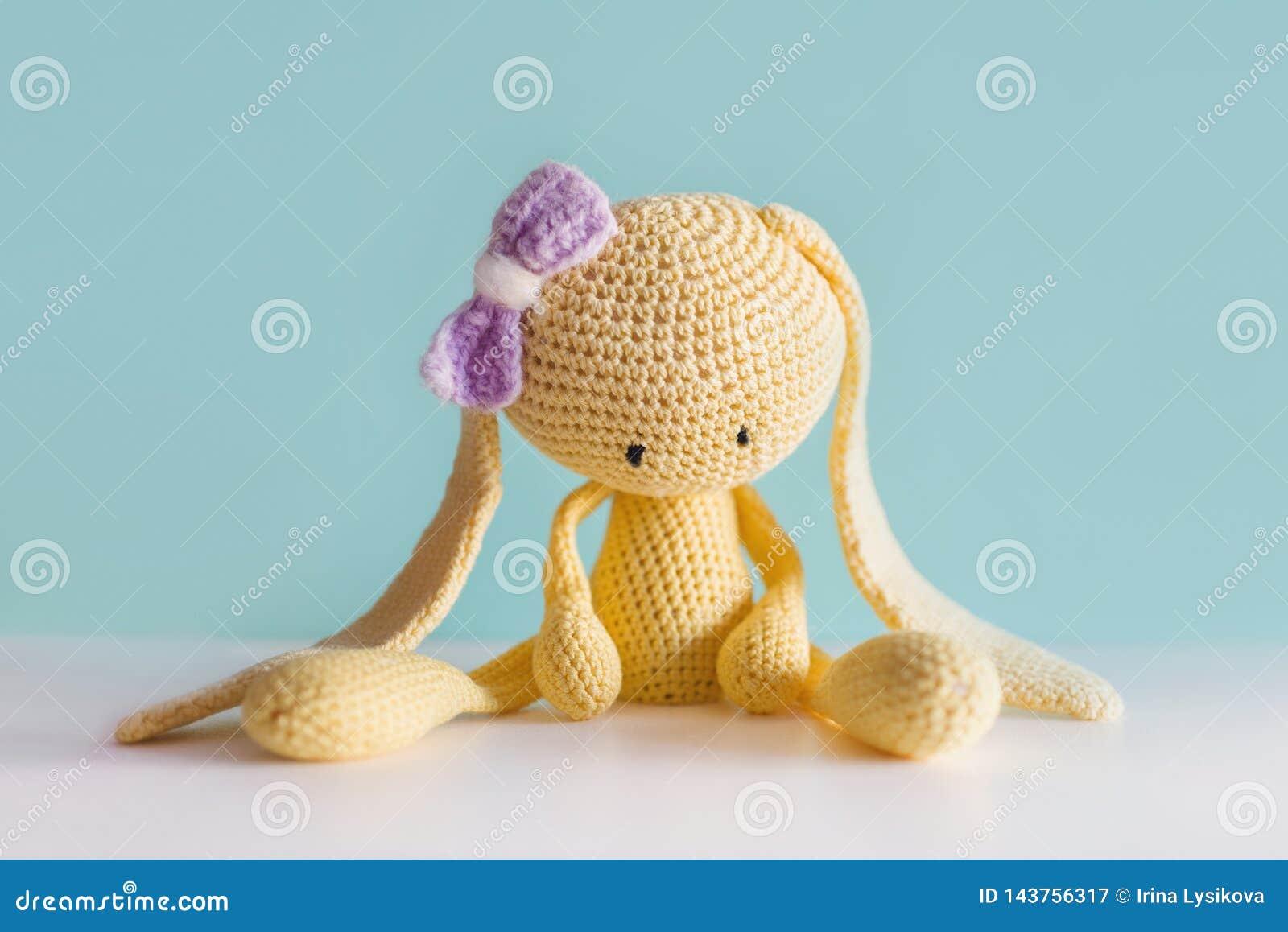 Zachte stuk speelgoed gebreide hazen Het zitten van gele droevige pluchehazen met een violette boog Amigurumi