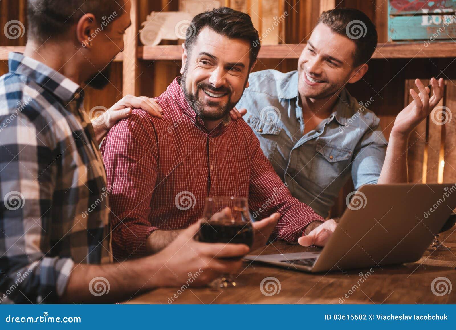 Zadowoleni ładni mężczyzna patrzeje ich przyjaciela