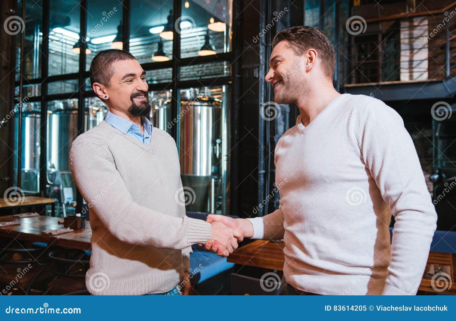Zadowoleni ładni mężczyzna trząść ręki
