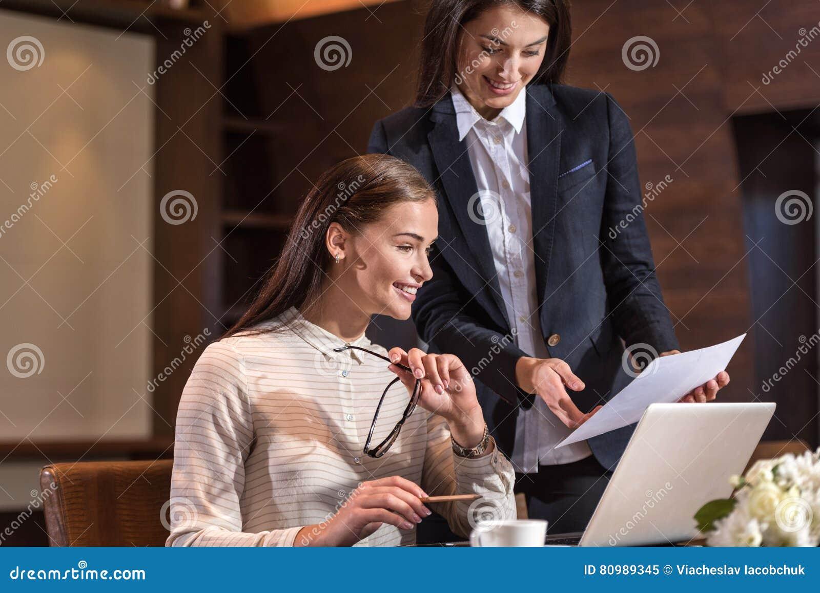 Zadowoleni żeńscy koledzy pracuje wpólnie w biurze