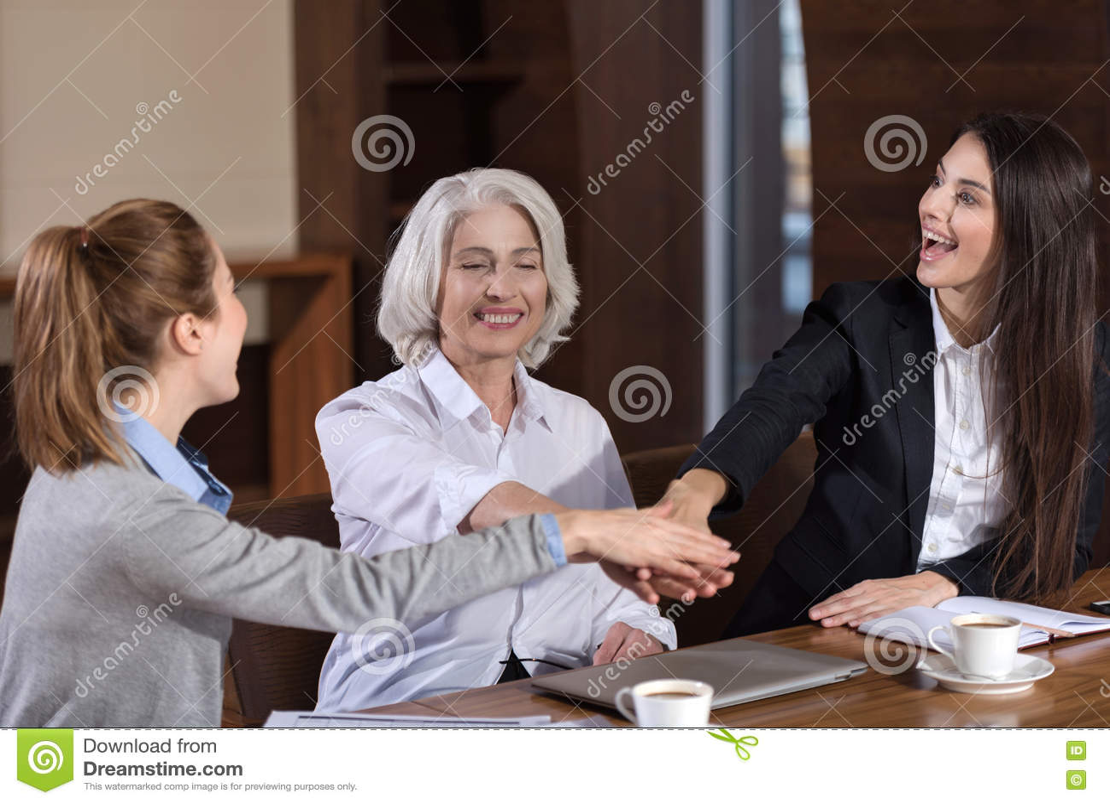 Zadowoleni koledzy trzyma each inny ręki