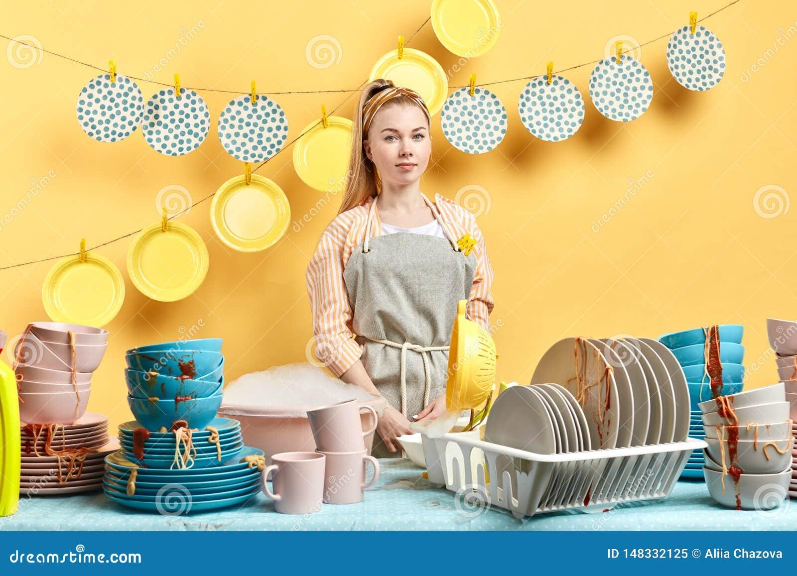Zadowolona atrakcyjna kobieta z życzliwym spojrzeniem czyści kuchnię