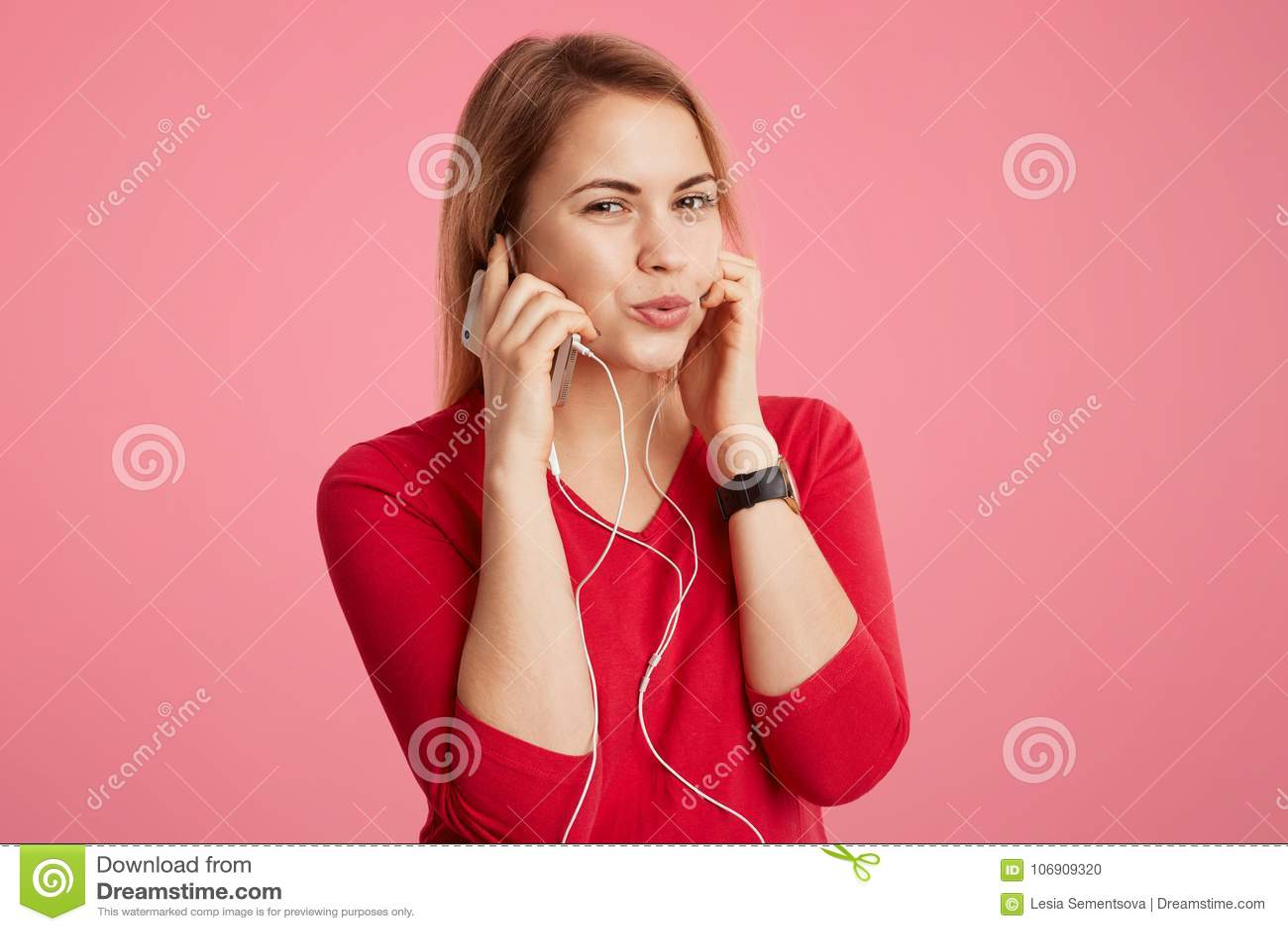 Zadowolona kobieta cieszy się pupila ślad w słuchawkach, używa nowożytnego gadżet, szczęśliwego słuchać przyjemną muzykę nad różo