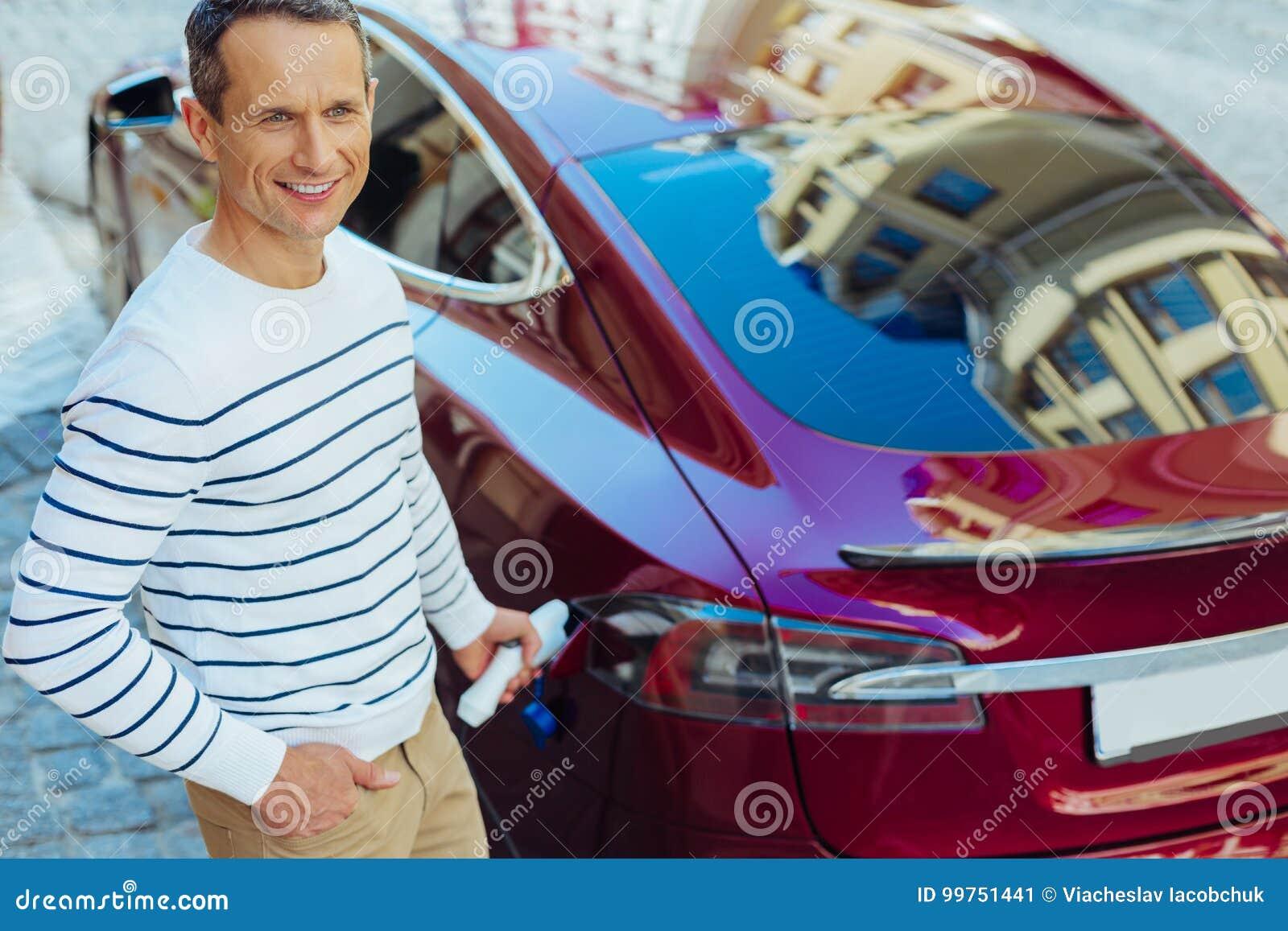 Zadowolony ładny mężczyzna stawia paliwowego nozzle w samochód