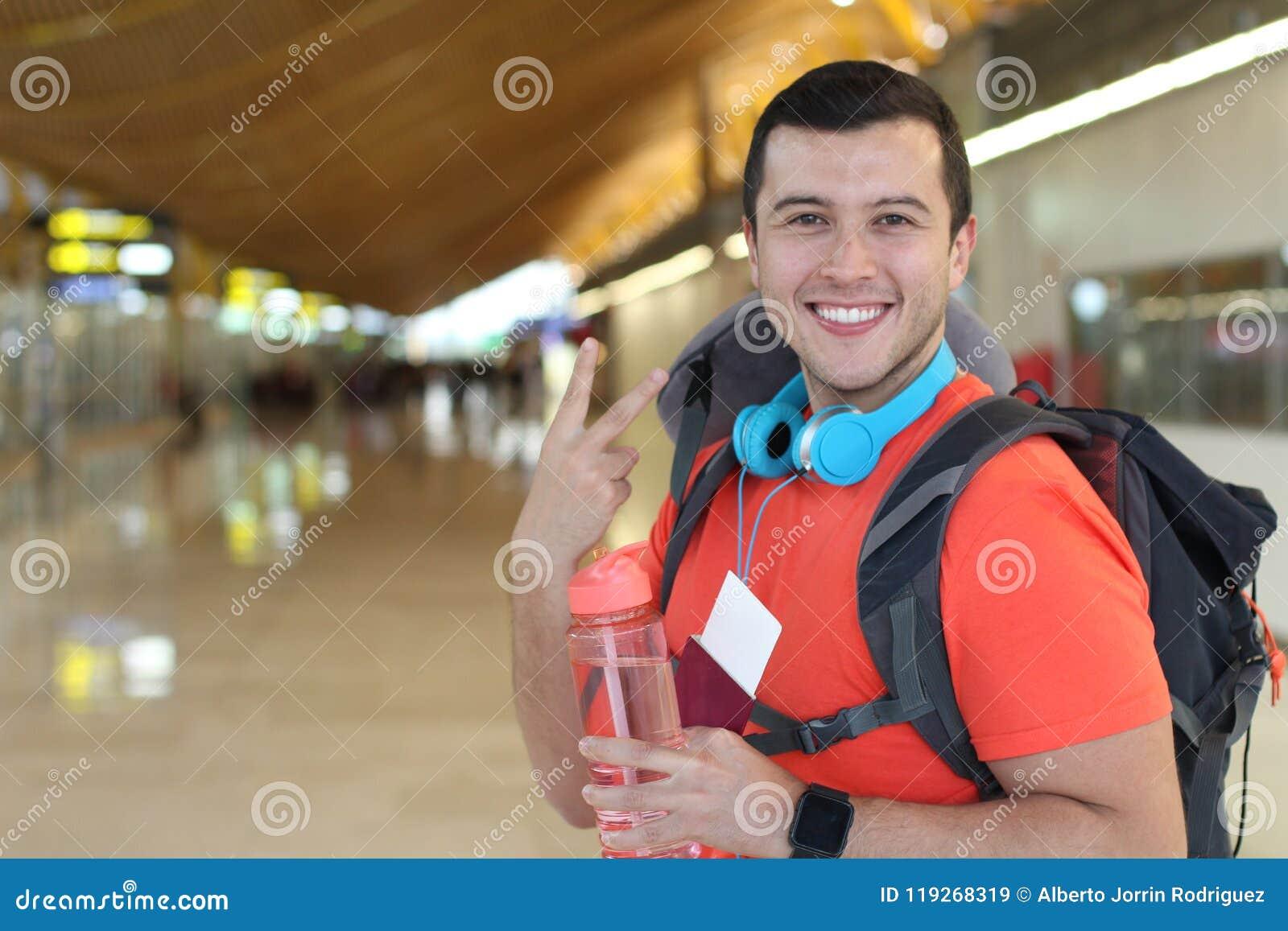 Zadowolony podróżnik daje pokoju znakowi od lotniska