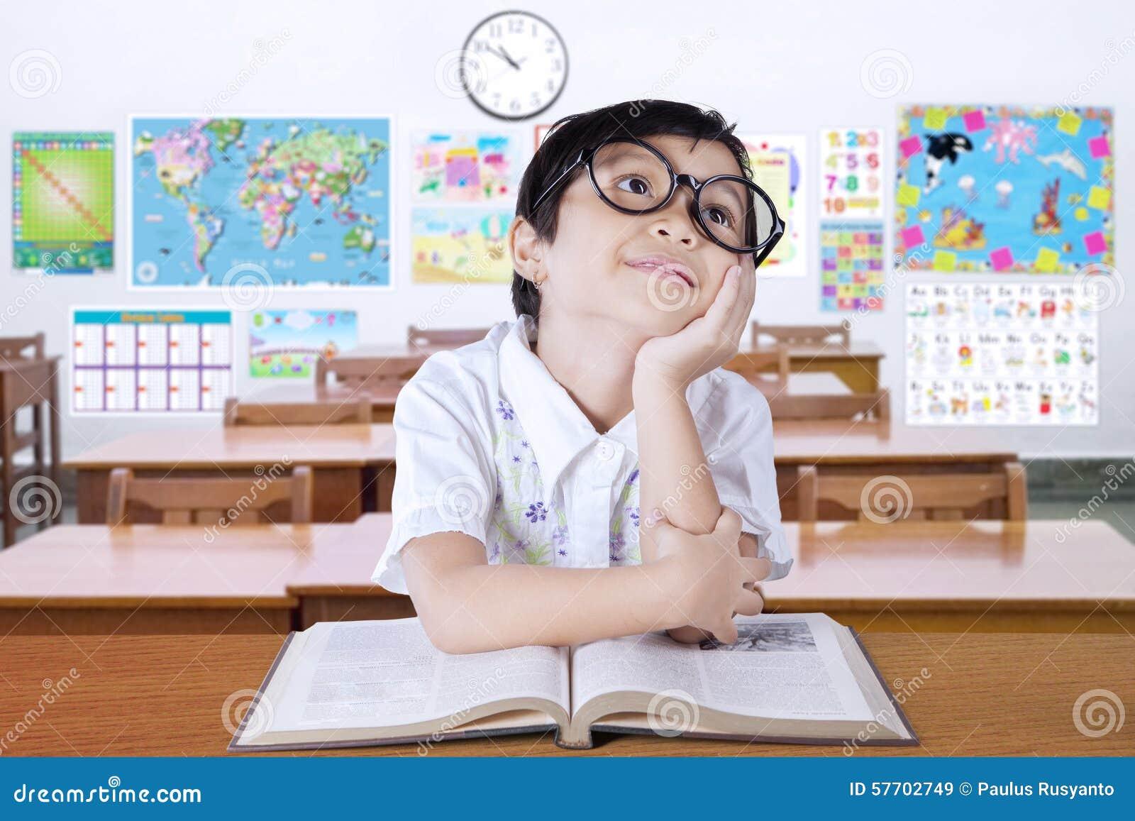 Zadumanego małego ucznia myślący pomysł w klasie