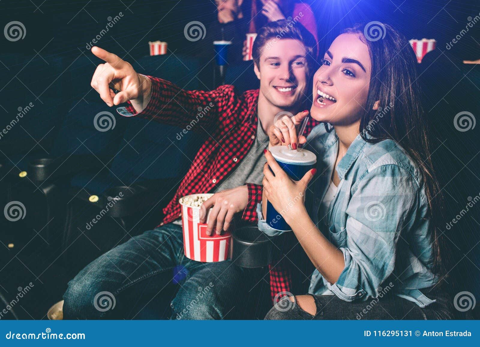 Zadziwiająca i rozochocona dziewczyna jest roześmiana Pije kolę od błękitnej filiżanki Facet chce chwytać jej wskazywać i uwagę