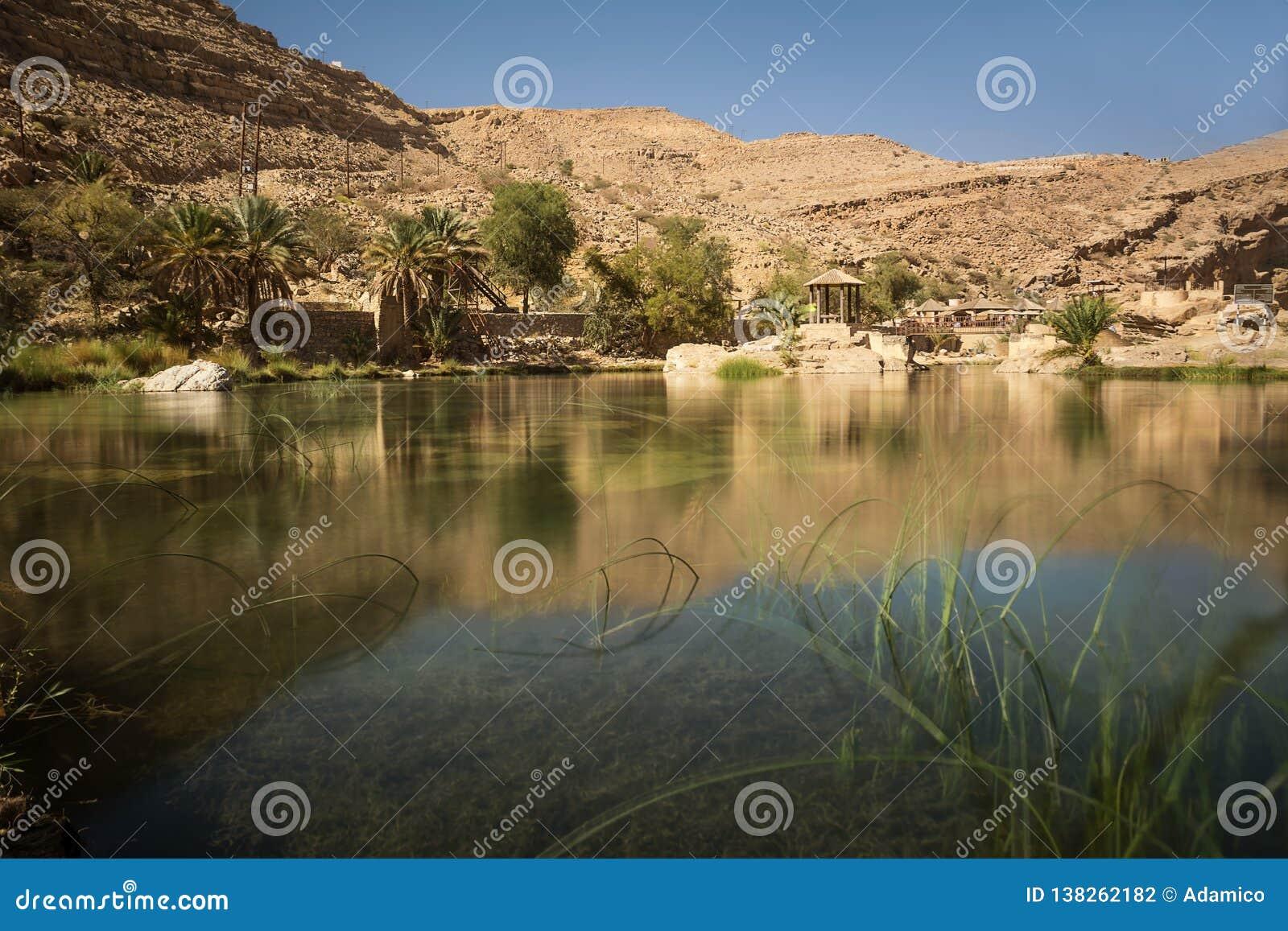 Zadziwiający jezioro i oaza z drzewko palmowe wadim Bania Khalid w Omani pustyni