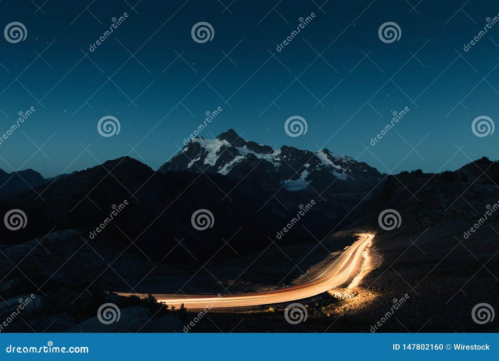 Zadziwiający nocne niebo z śnieżne skaliste góry w środku i dimly zaświecającej drodze