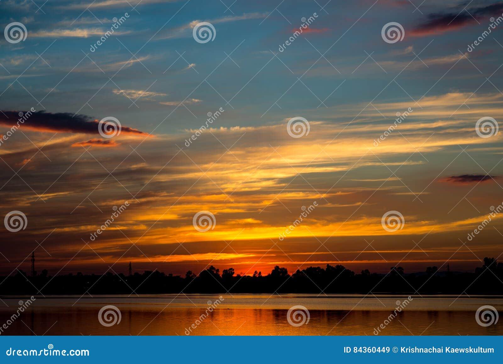 Zadziwiający złoty zmierzchu niebo z odbiciem na spokojnym jeziorze