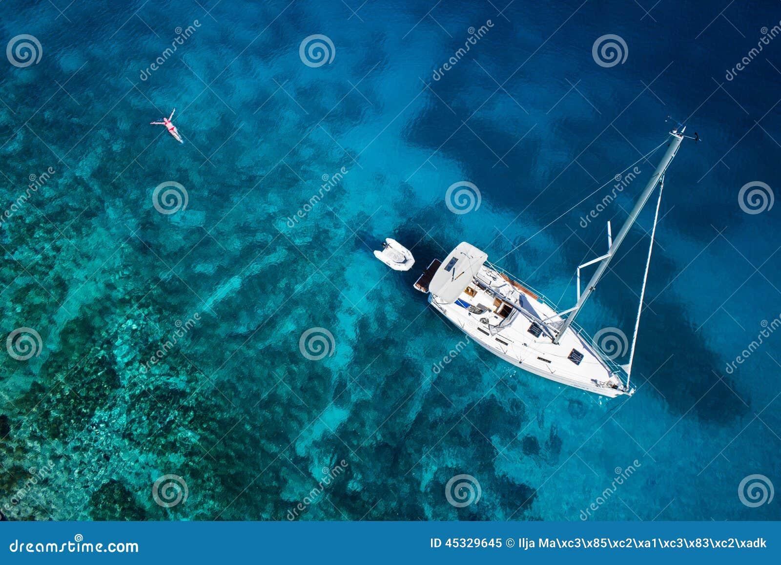 Zadziwiający widok jacht, pływacka kobieta i jasnego wodny karaibski,