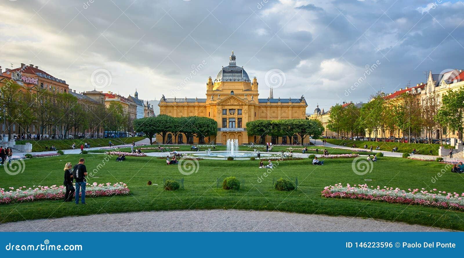 Zagreb, Chorwacja, Kwiecień 24, 2019: Ludzie cieszy się w ładnym wiosna dniu w parkowym sztuka pawilonie w kolorowym parku