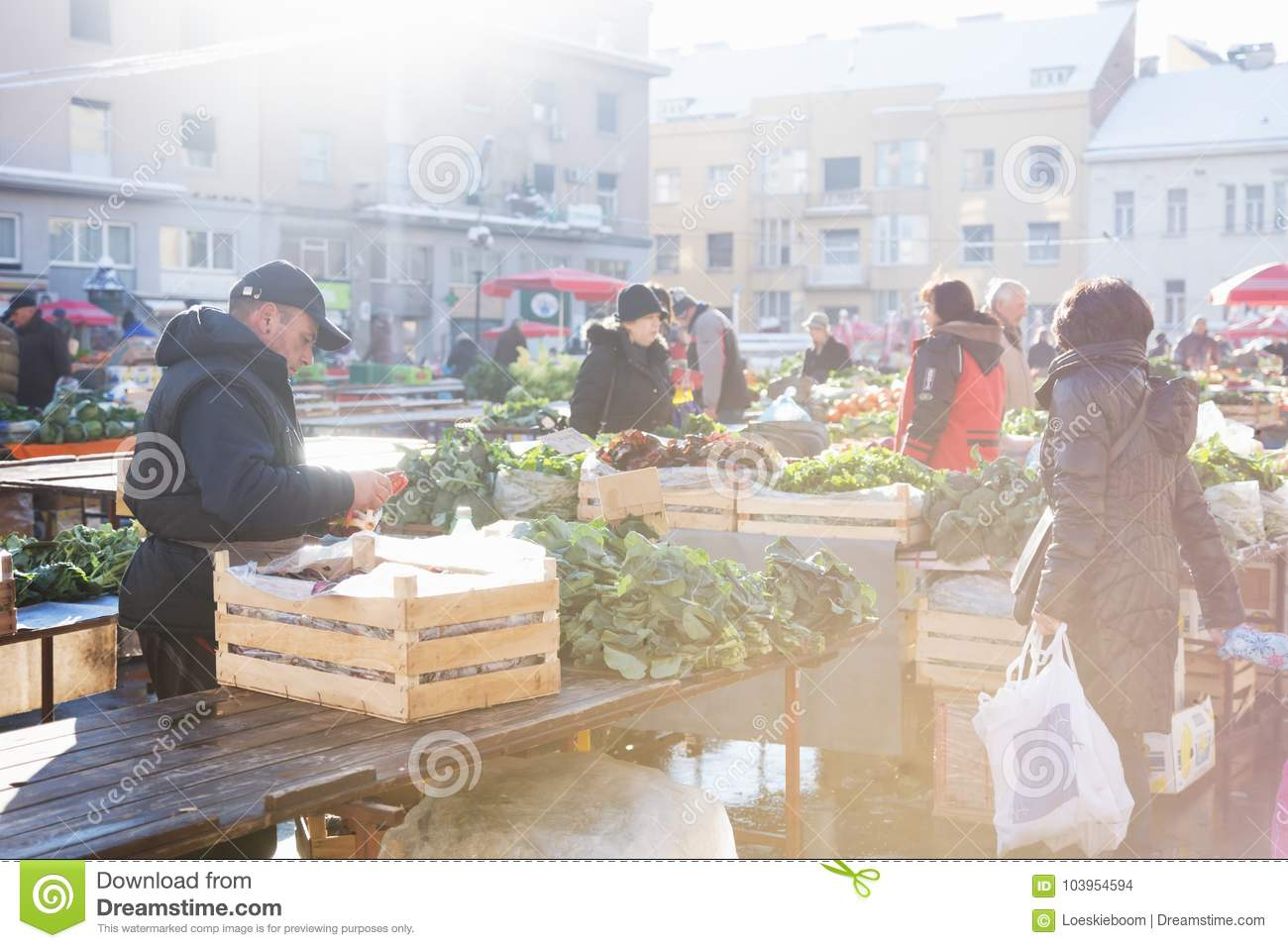 Zagreb, Croatia: January 7 2016: Man sorting out vegetables at Dolac market during wintertime with snow